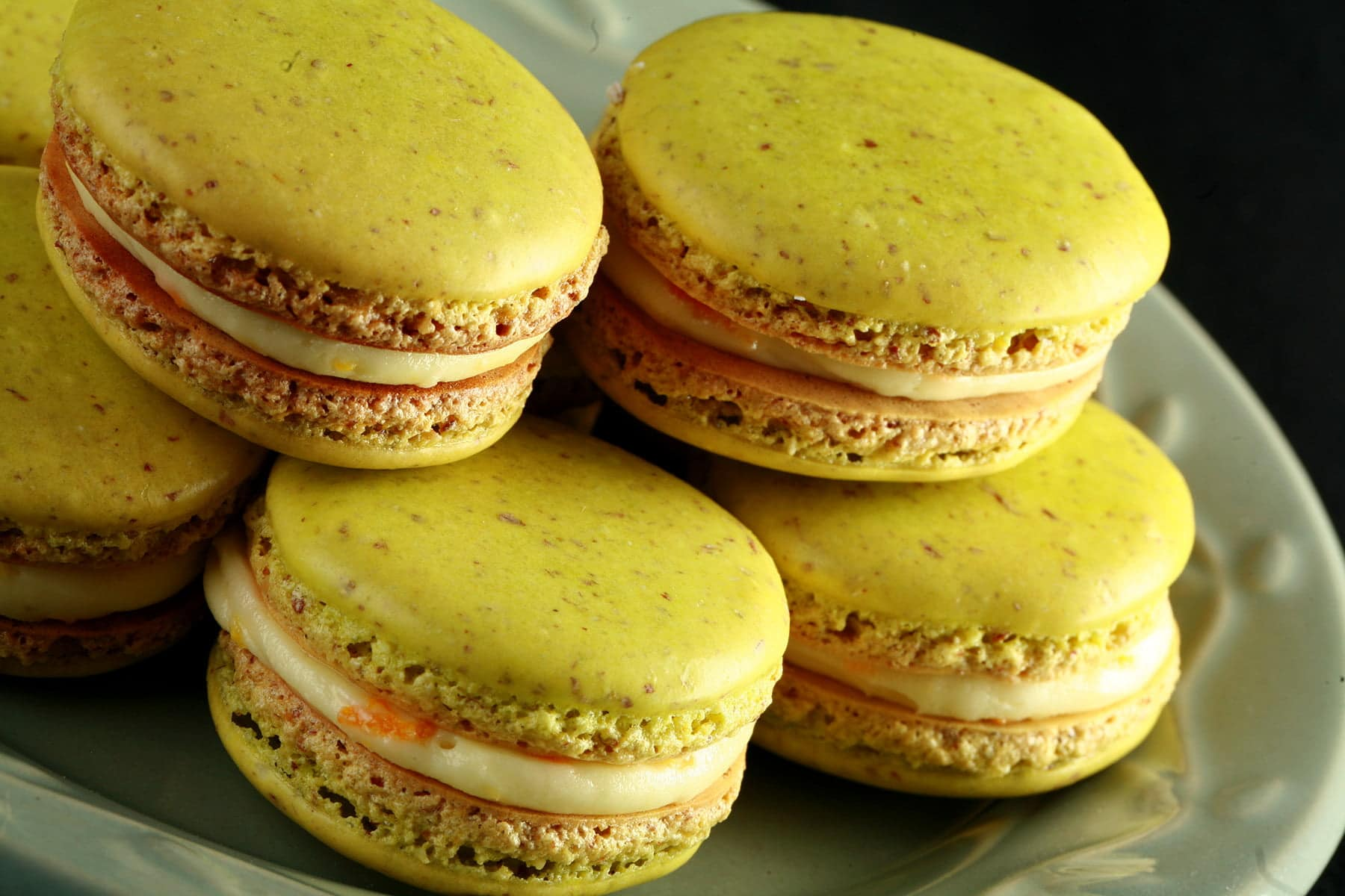 A small green plate is piled high with bright lime green Citrus Hop Macarons. There is a fresh hop flower on the plate, and bits of orange zest visible in the filling of the macarons.
