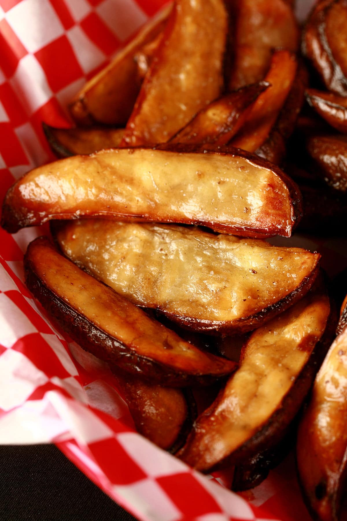 A red basket lined with red and white checkerboard paper holds a batch of smoked french fries that have been cooked in an air fryer.