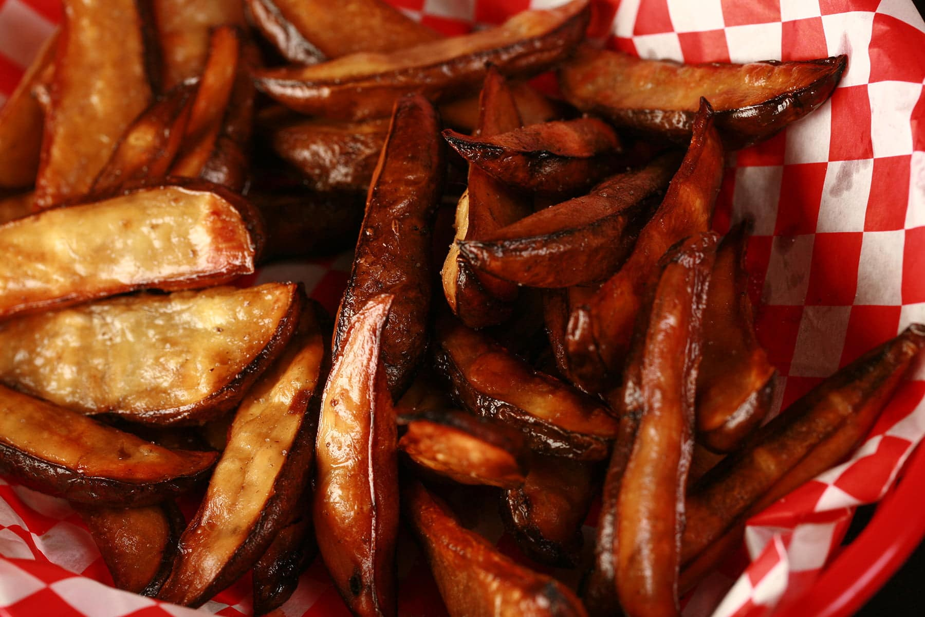 A red basket lined with red and white checkerboard paper holds a batch of smoked fries that have been cooked in an air fryer.