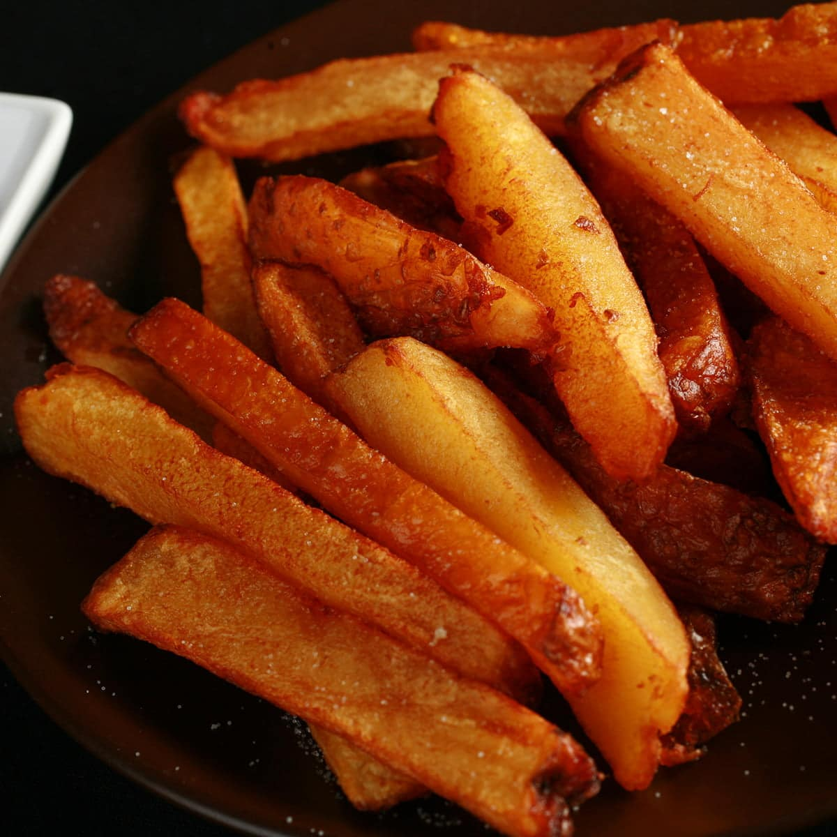 A plate of smoked french fries, with a small bowl of ketchup on the side.