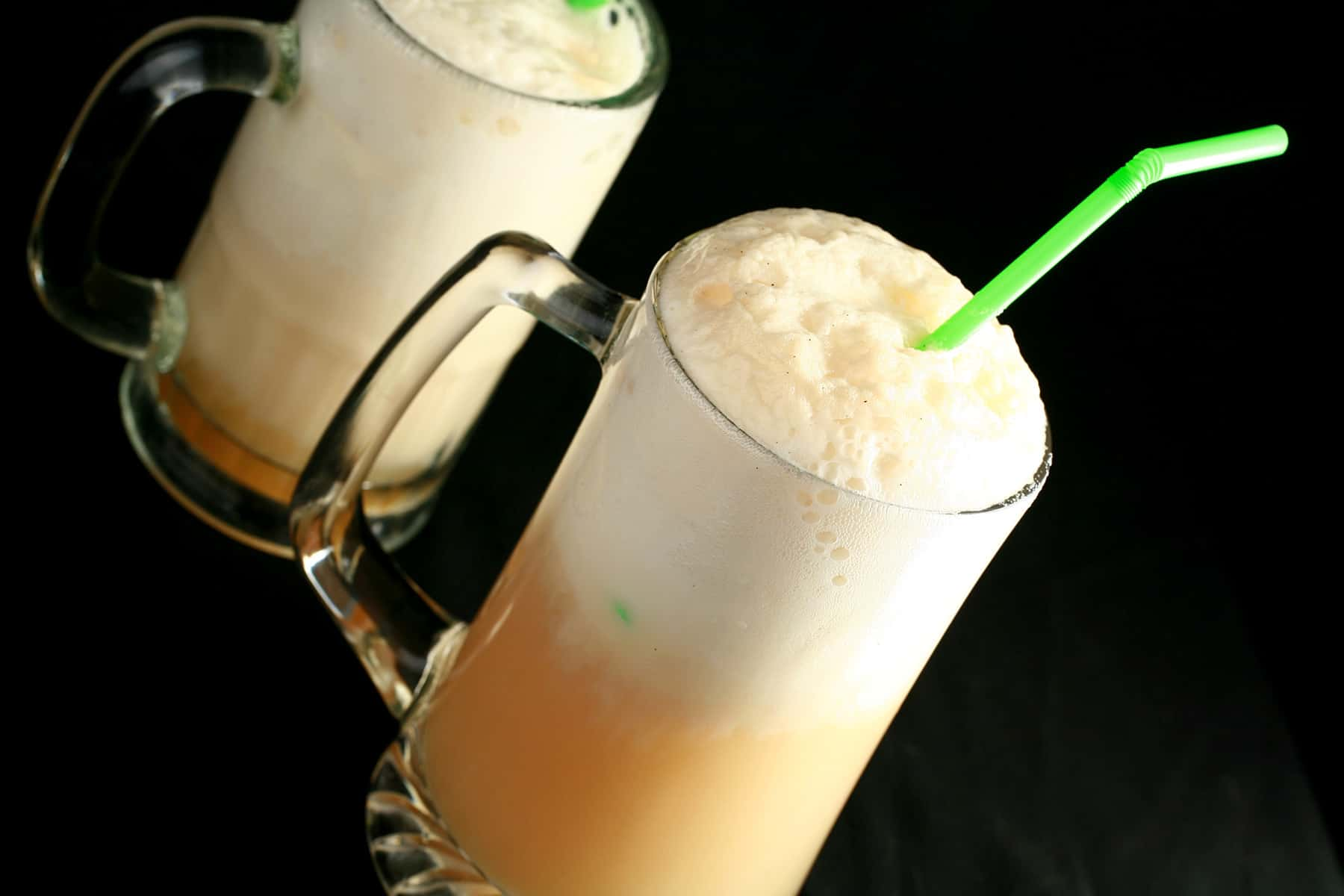 Two tall beer steins with sparkling cider floats in them.