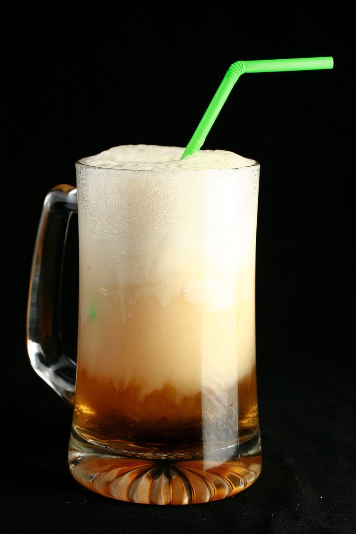 A tall beer stein with a sparkling apple cider float in it.