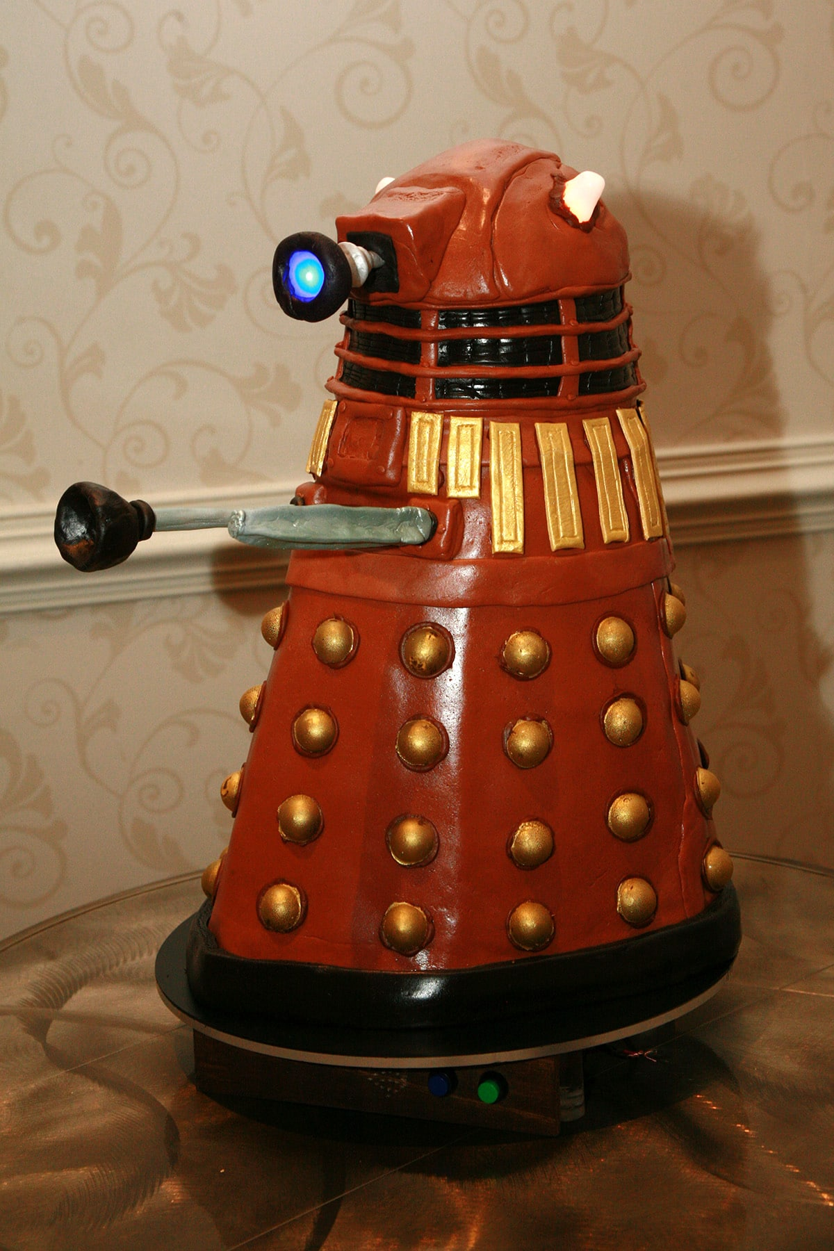 A brown Dalek cake on a hotel table.