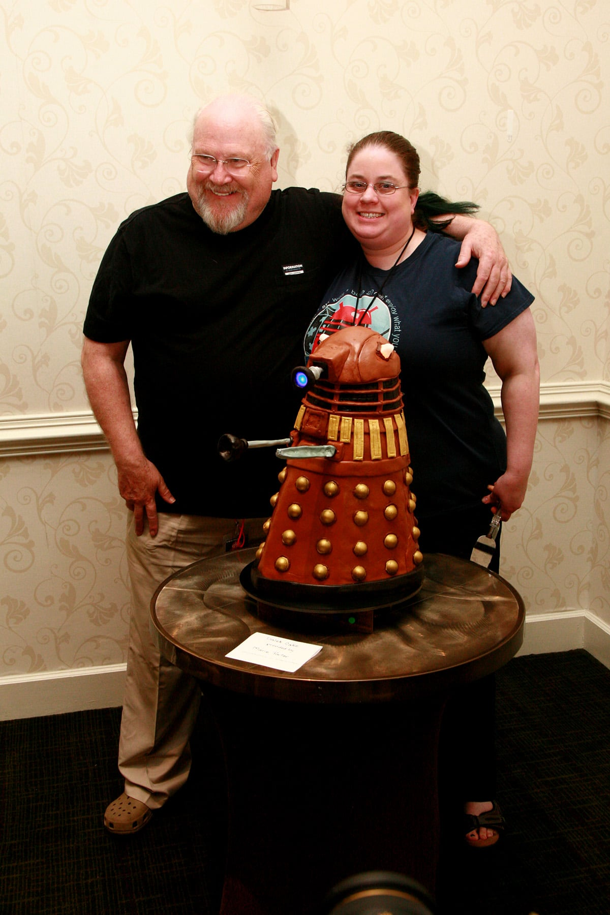 Colin Baker and Marie Porter pose behind the Dalek cake.