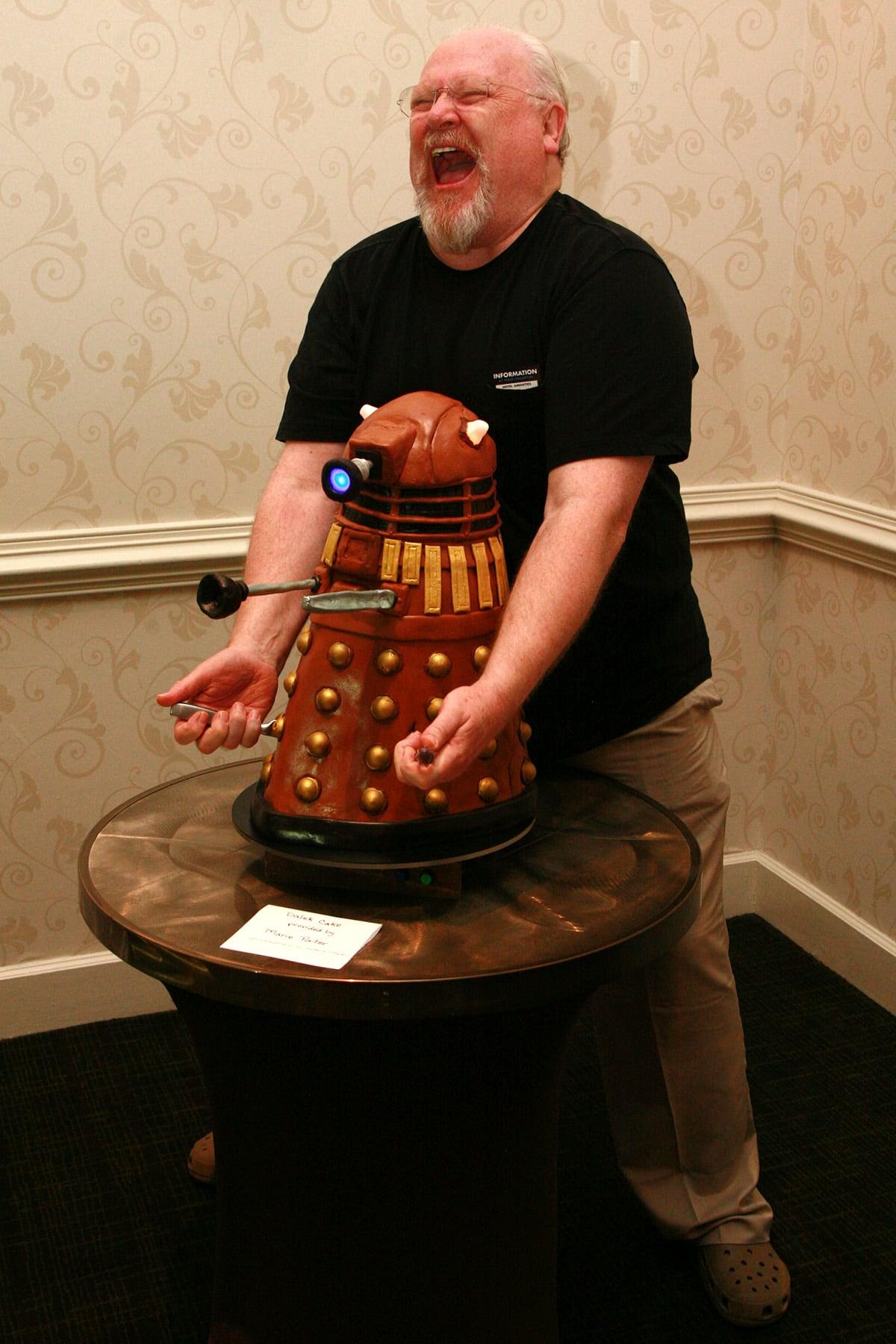 Colin Baker jams 2 serving knives into the Dalek Cake while posing.