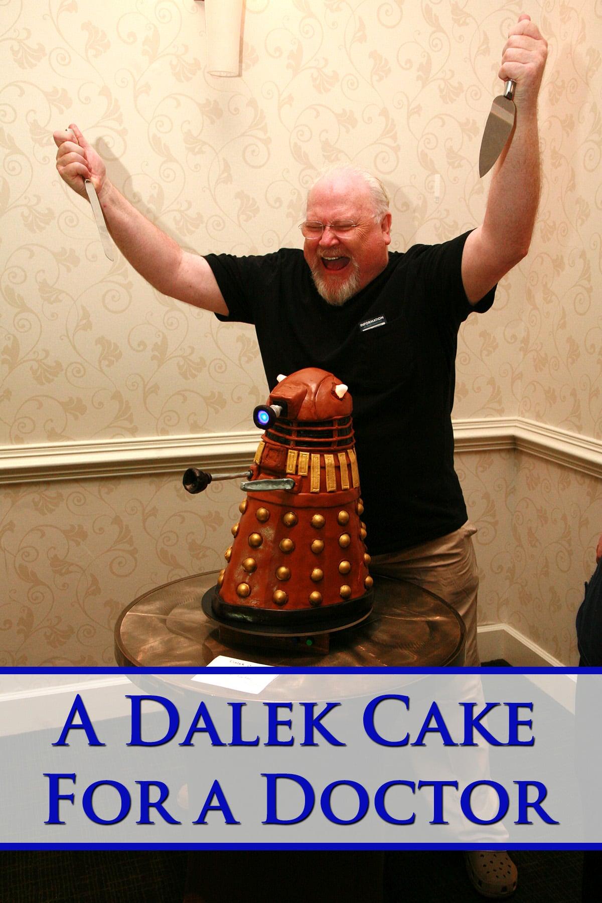 Colin Baker posing behind the Dalek cake, knives raised.