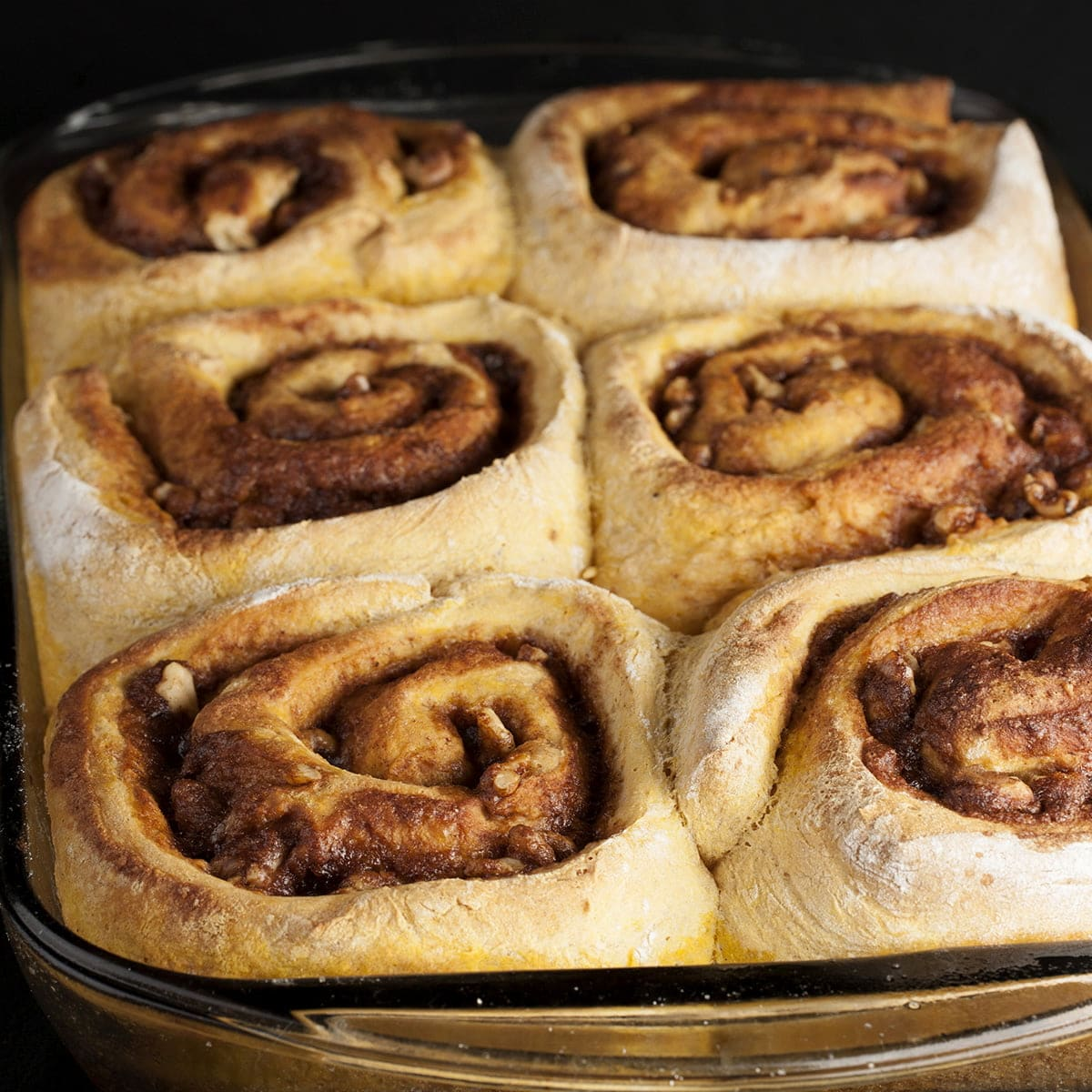 A rectangular baking pan with 6 very large Maple Spiced Pumpkin Buns in it.