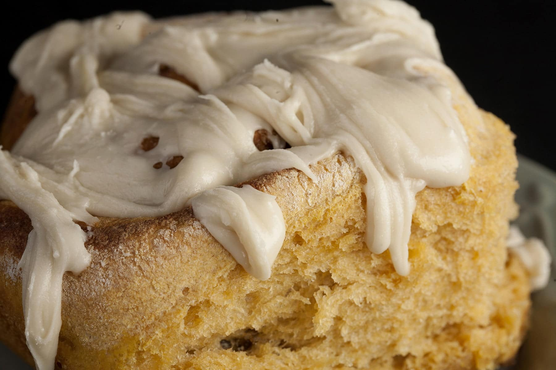 A large maple pumpkin spiced bun - like a cinnamon roll - on a plate. It is covered in a white frosting.