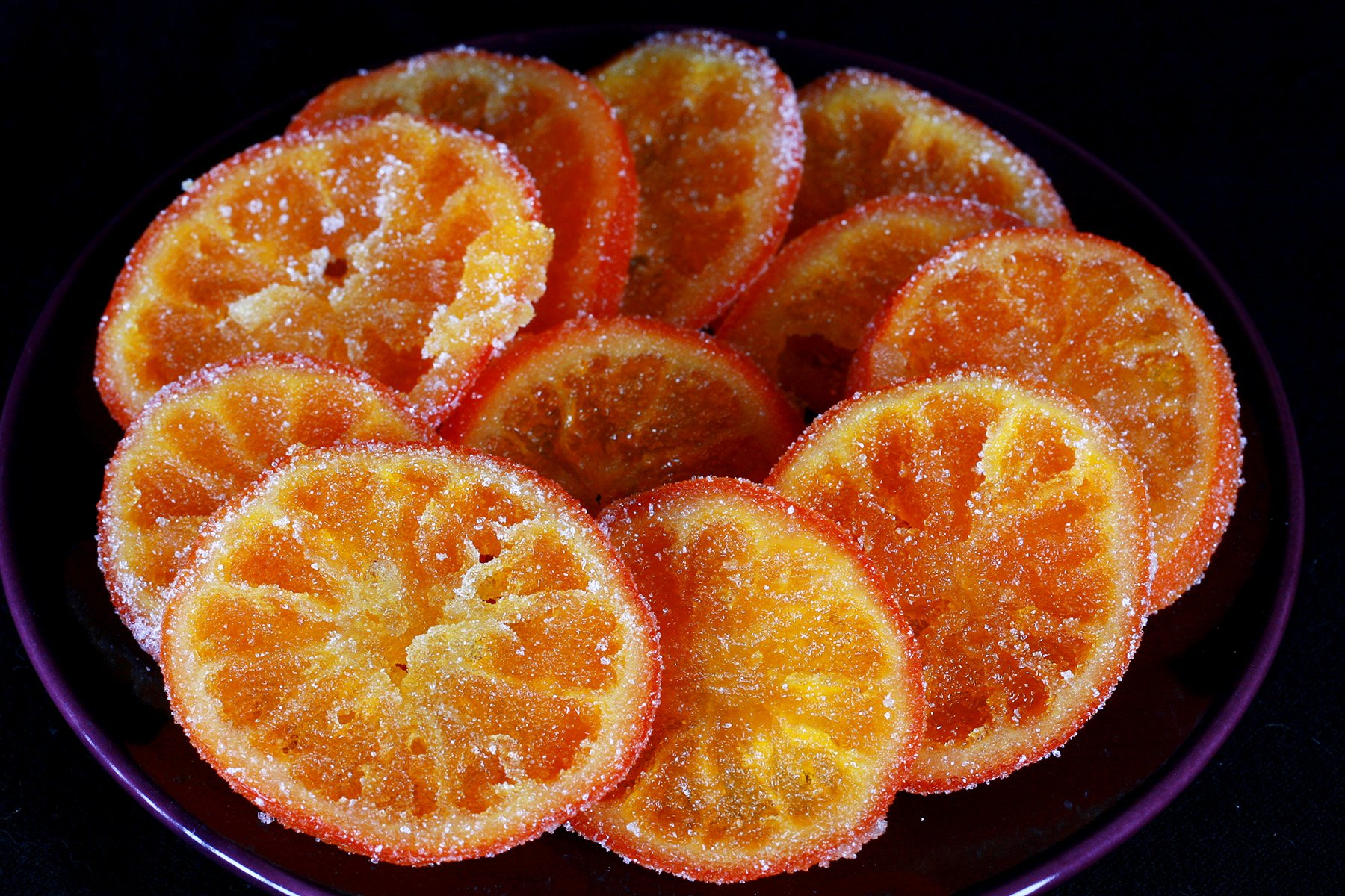A small blue plate with slices of candied oranges spread out on it.