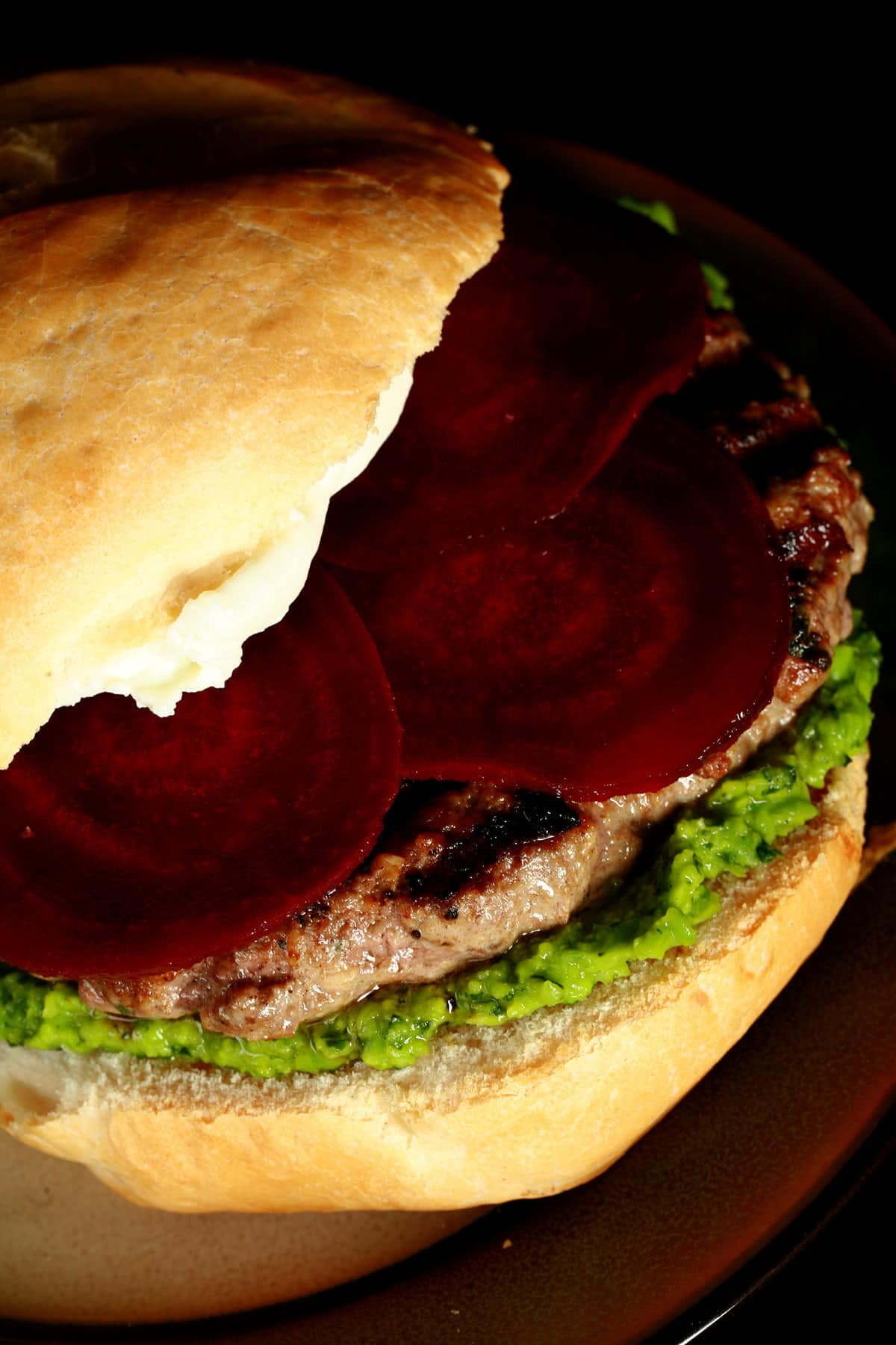 Close up view of a burger with a green spread, a goat cheese spread, and beet slices on it.