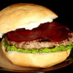 Close up view of a moroccan spiced lamb burger with a green spread, a goat cheese spread, and beet slices on it.