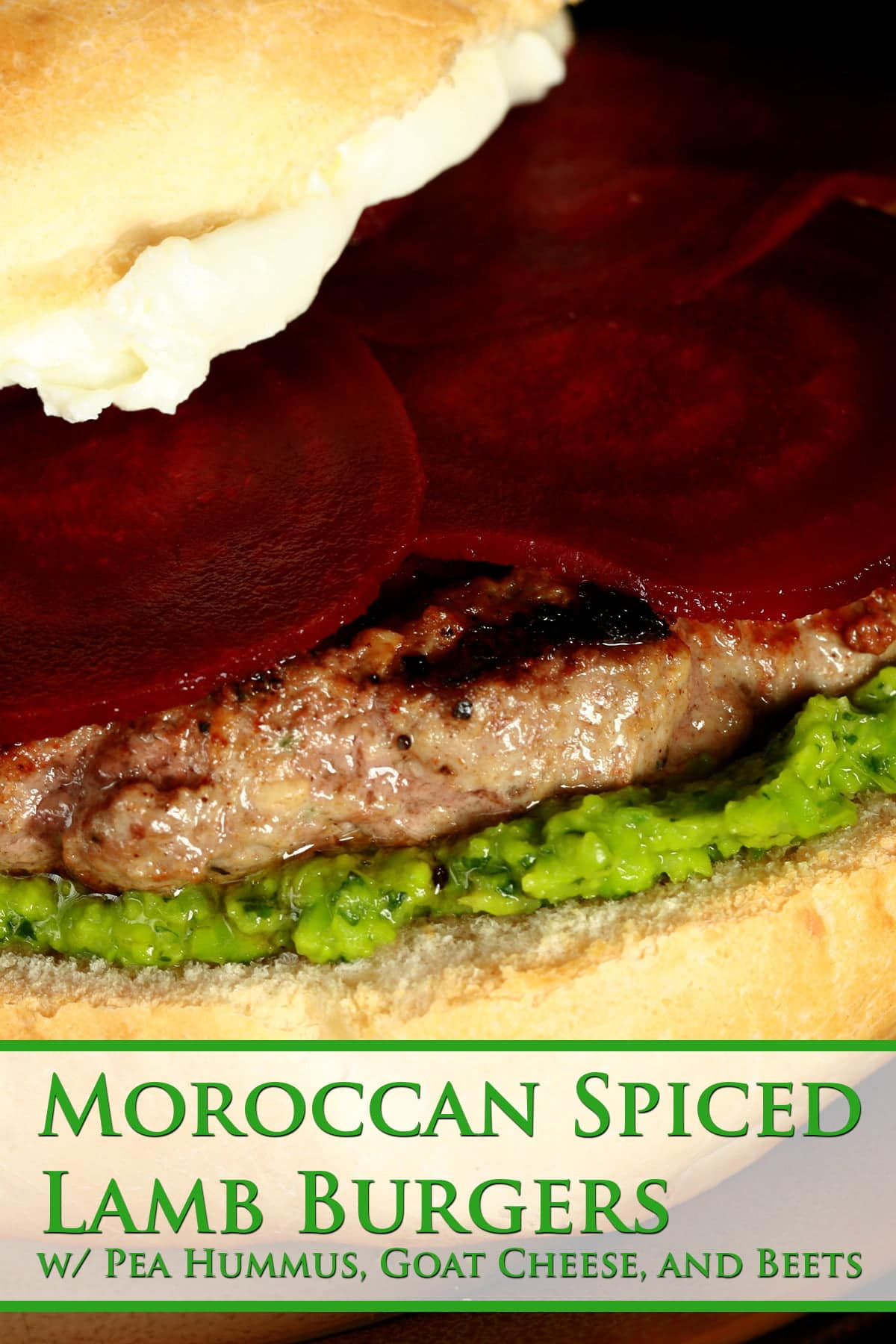 Close up view of a lamb burger with a green spread, a goat cheese spread, and beet slices on it.