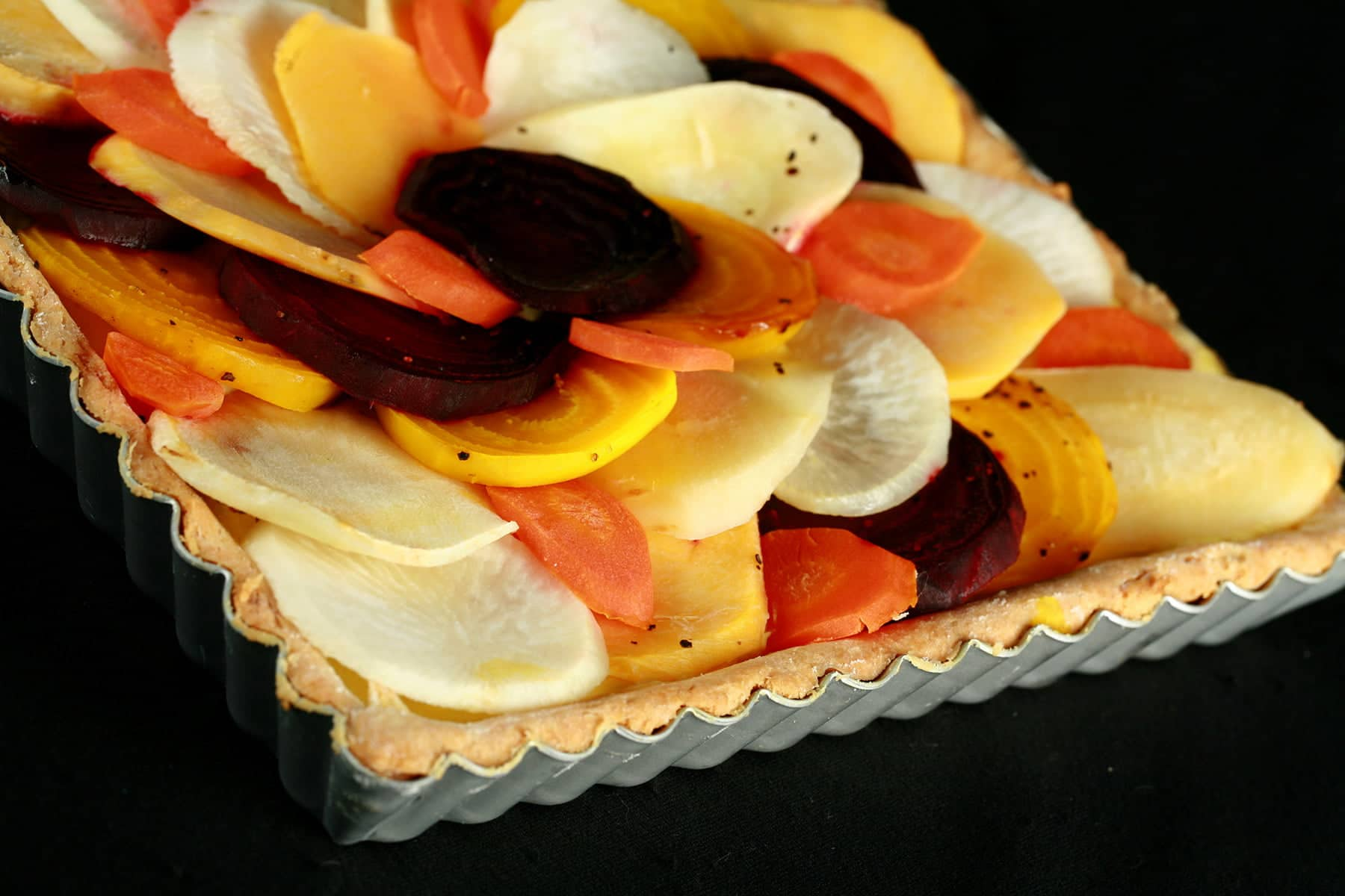 A close up view of a square root tart - a tart cooked in a square pan, with slices of a variety of root veggies arranged on top.