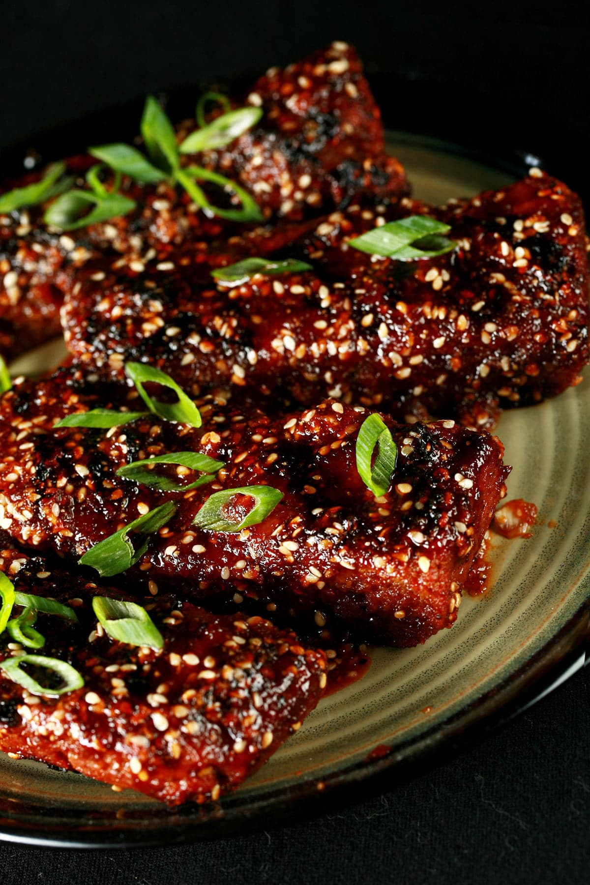 Close up photo of a plate of vegan boneless ribs. They're covered in a red-brown sauce, sesame seeds, and sliced green onion.