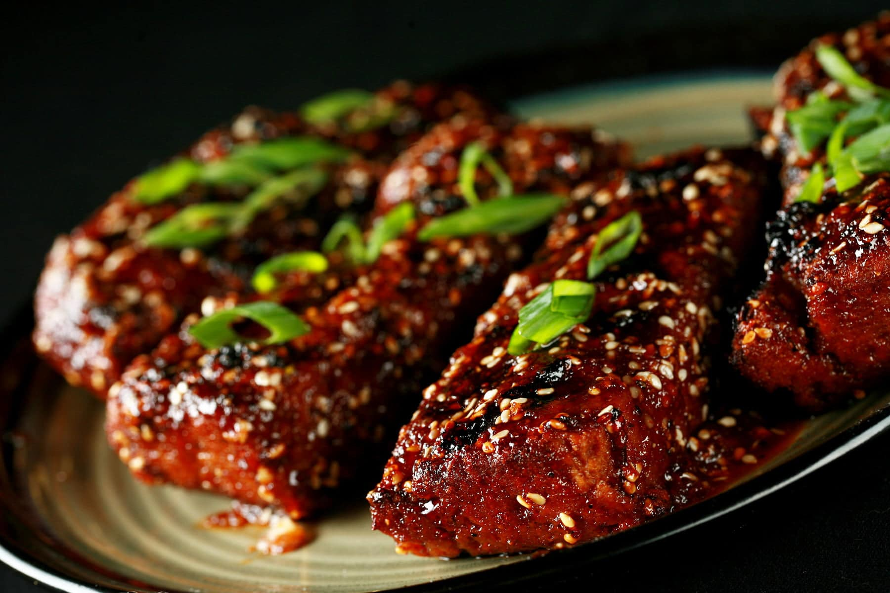 Close up photo of a plate of vegetarian boneless ribs. They're covered in a red-brown sauce, sesame seeds, and sliced green onion.