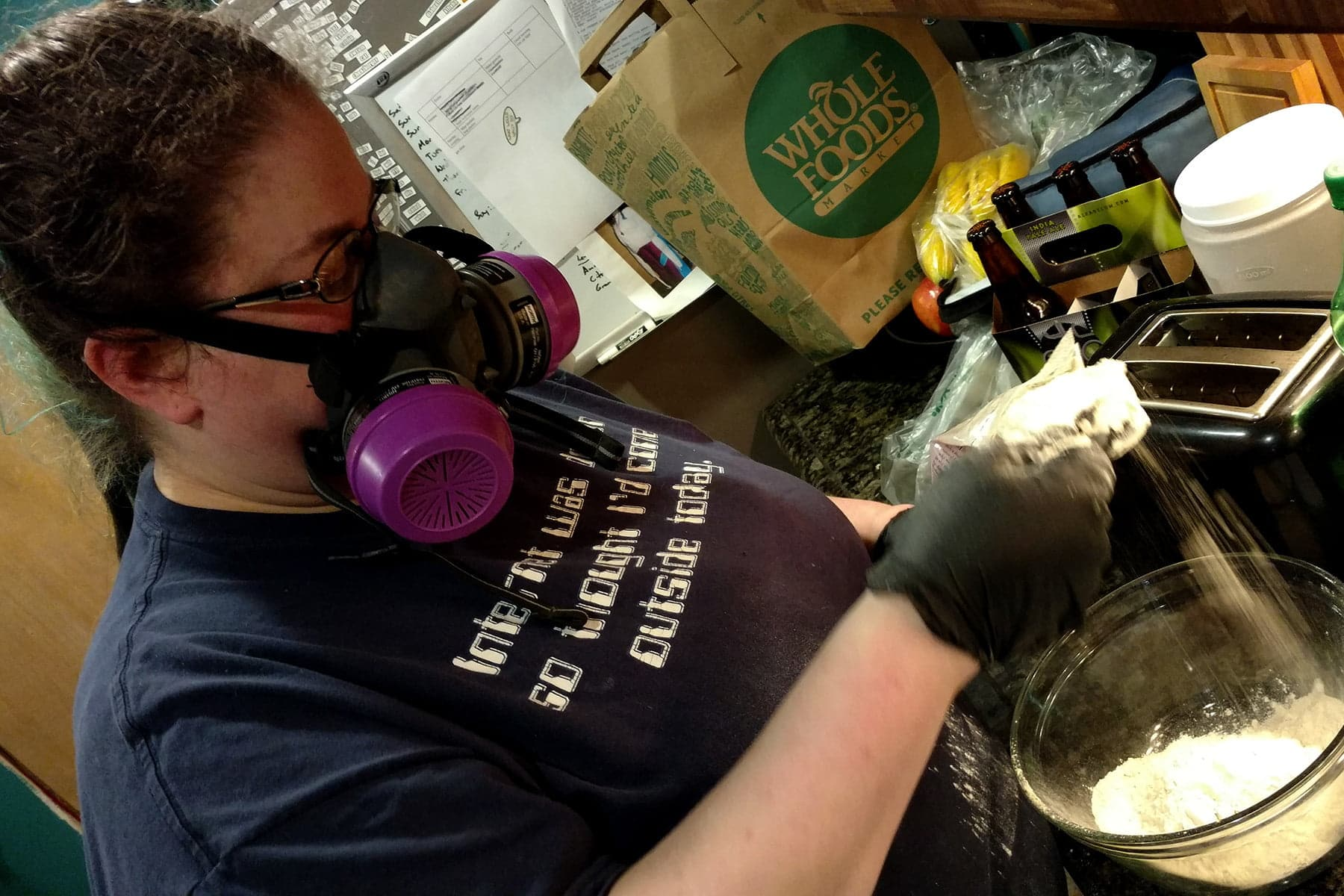 The author is pictured wearing a dark blue shirt and a half mask. She is wearing black nitrile gloves while handling vital wheat gluten.