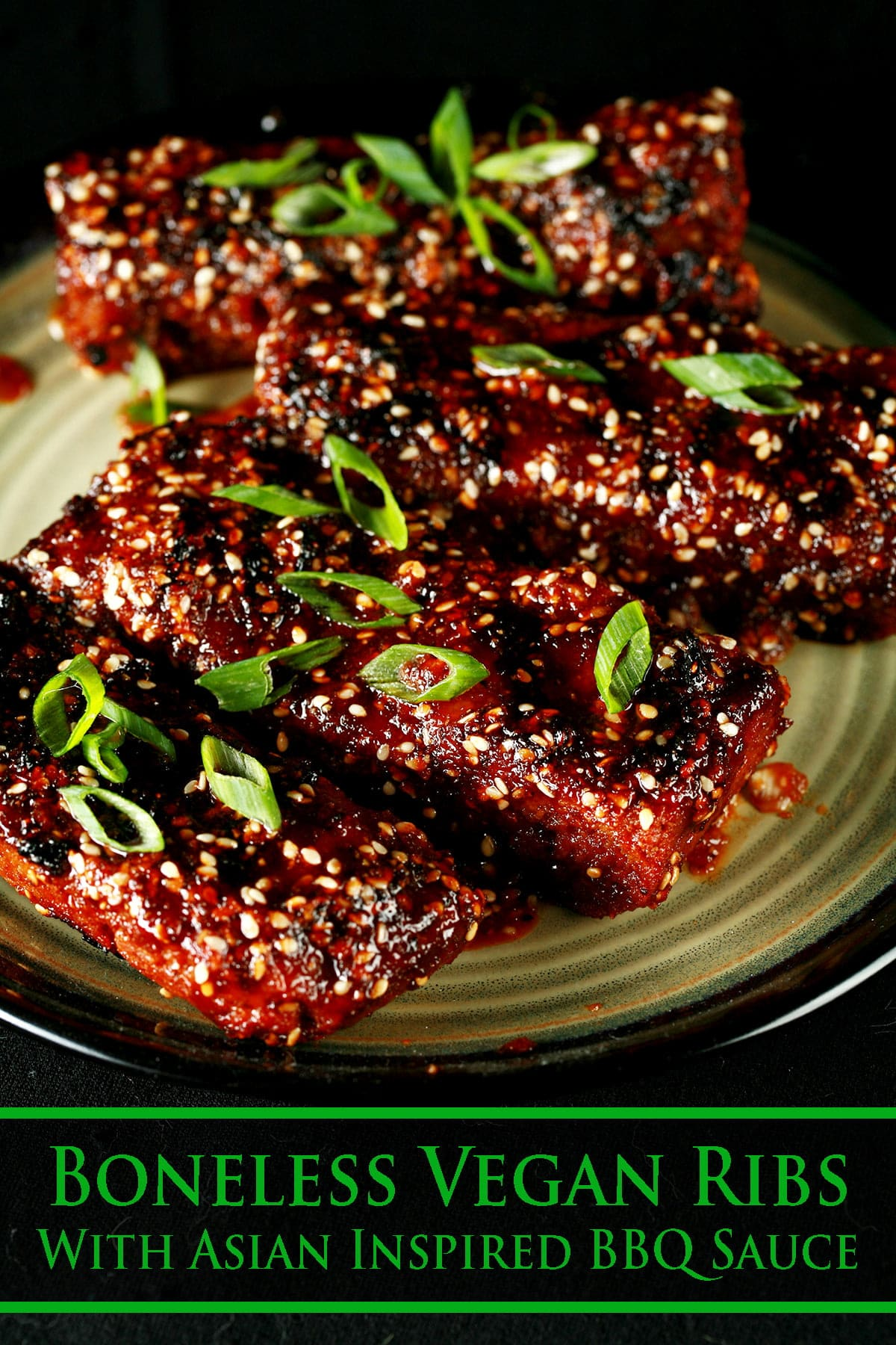 Close up photo of a plate of boneless ribs. They're covered in a red-brown sauce, sesame seeds, and sliced green onion.