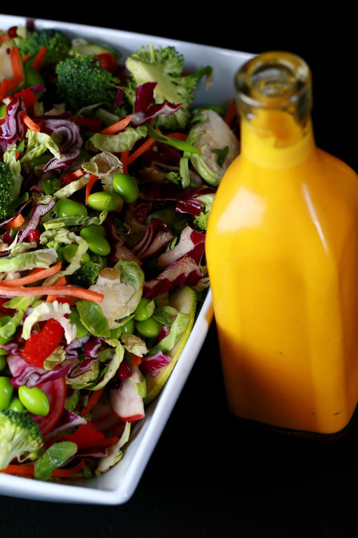A close up view of rainbow salad. Cucumber slices, edamame, red peppers, carrot, purple cabbage, and red onions are all visible. The salad is in a large white bowl, with a bottle of a bright orange carrot ginger dressing next to it.