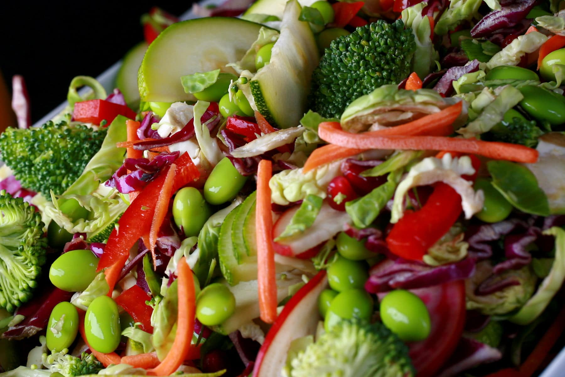 A close up view of rainbow salad. Cucumber slices, edamame, red peppers, carrot, purple cabbage, and red onions are all visible.