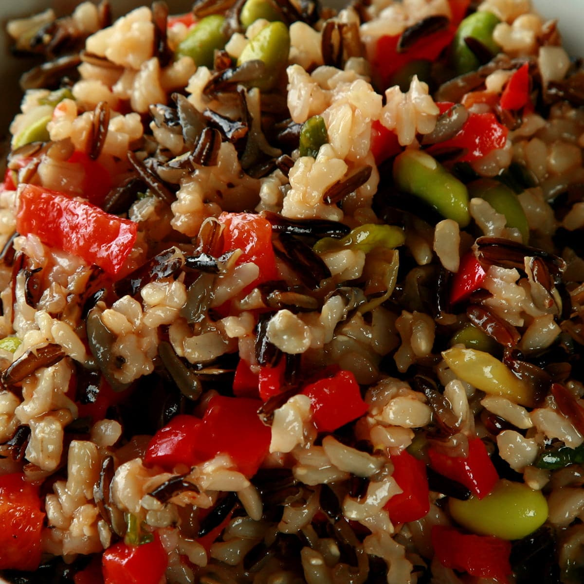 A bowl of wild rice and edamame salad. Wild rice, edamame, and red peppers are all visible.