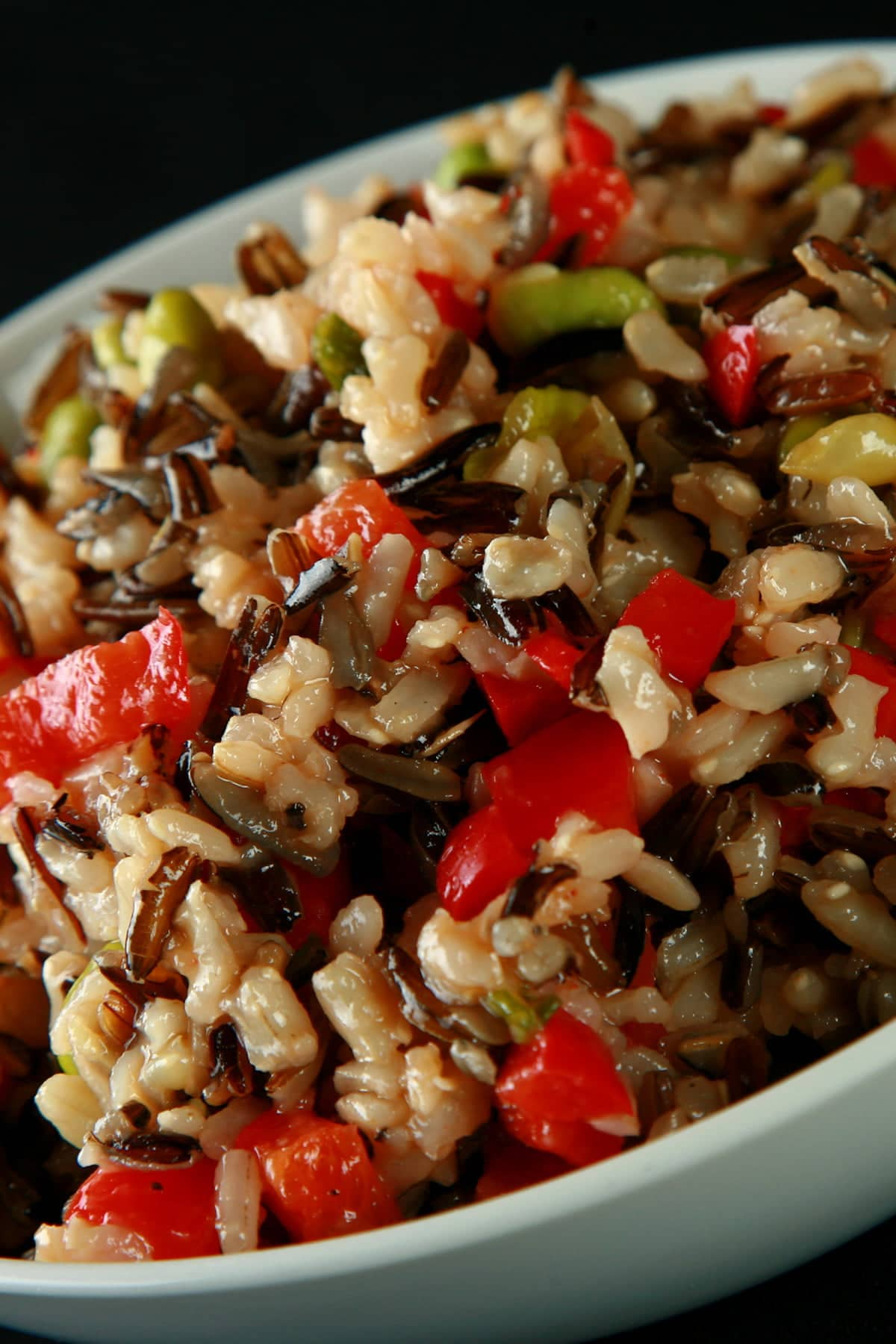 A bowl of edamame wild rice salad. Wild rice, edamame, and red peppers are all visible.