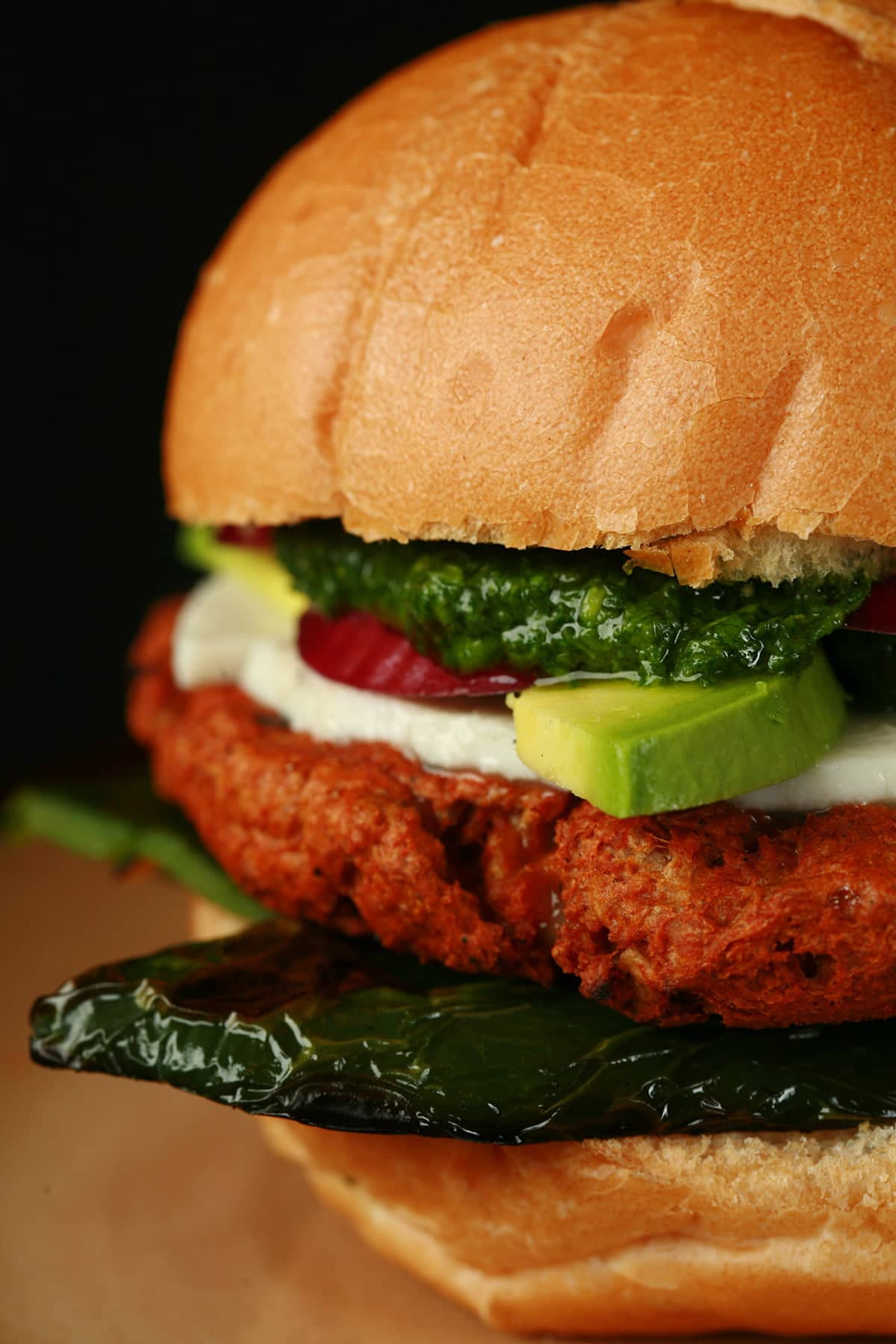 A close up view of a fully decked out vegetarian chorizo burger. Aside from the patty, a slice of roasted poblano, slices of red onion, a white cheese, and avocados are seen. A deep green cilantro pesto tops it all off.