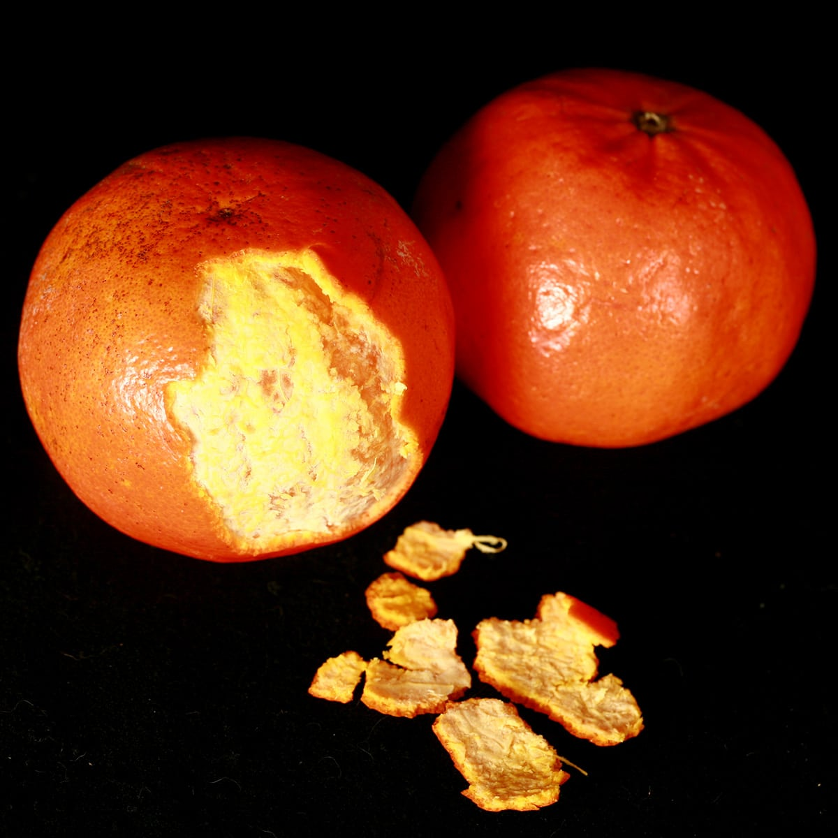 2 Sunburst Tangerine oranges, one peeled.