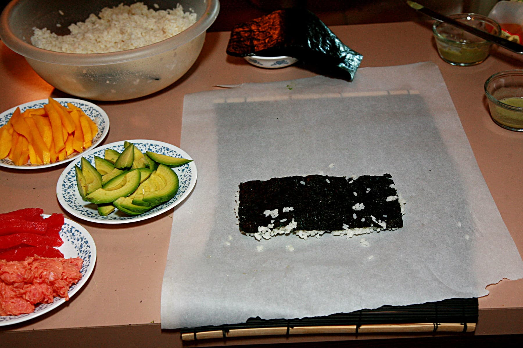 A sushi rolling station. A piece of nori with rice is laid out on a piece of parchment paper, with various sushi fillings laid out on plates next to it.