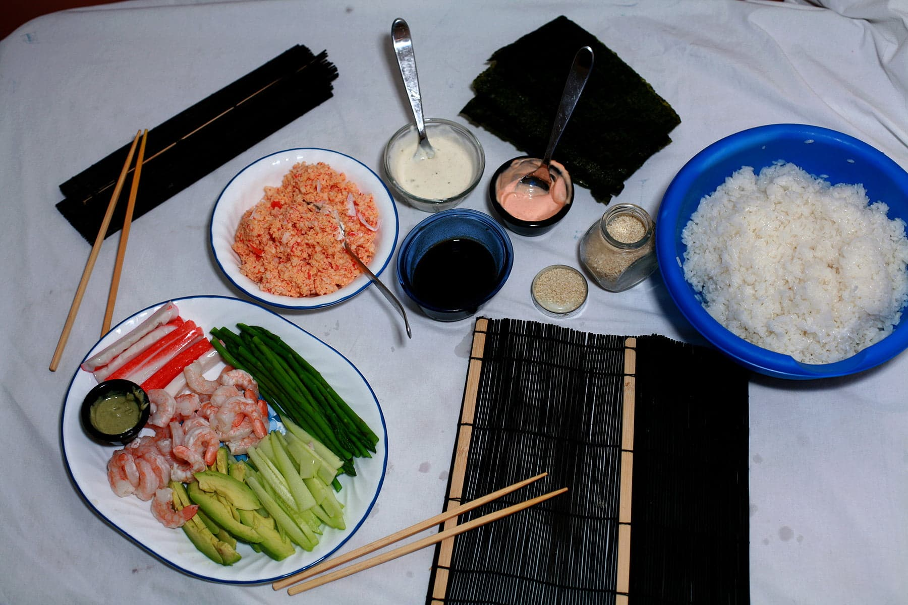 Various sushi fixings are shown laid out on a paper-lined table. There are plates of fillings, a bowl of rice, a stack of nori seets, and wrapping utensils.