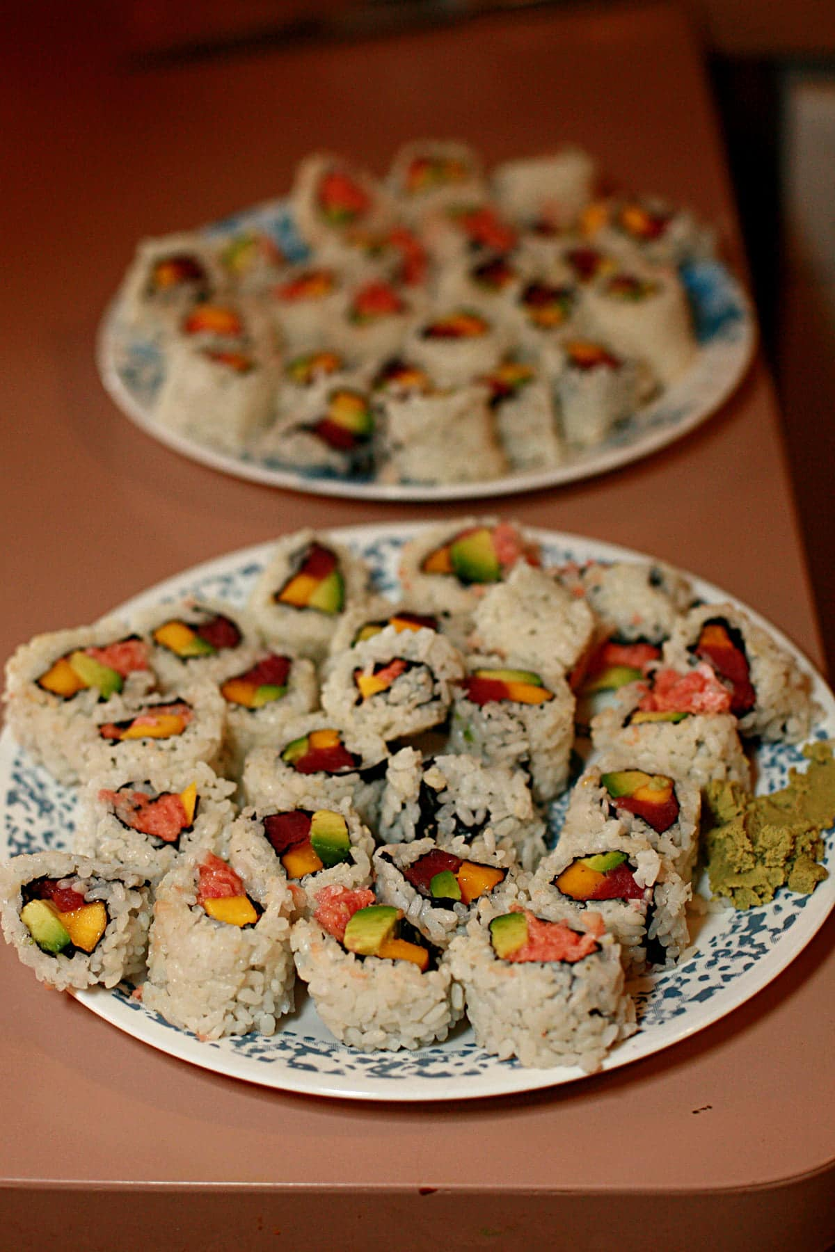 Two plates with dozens of pieces of DIY  sushi are shown on a pink countertop.