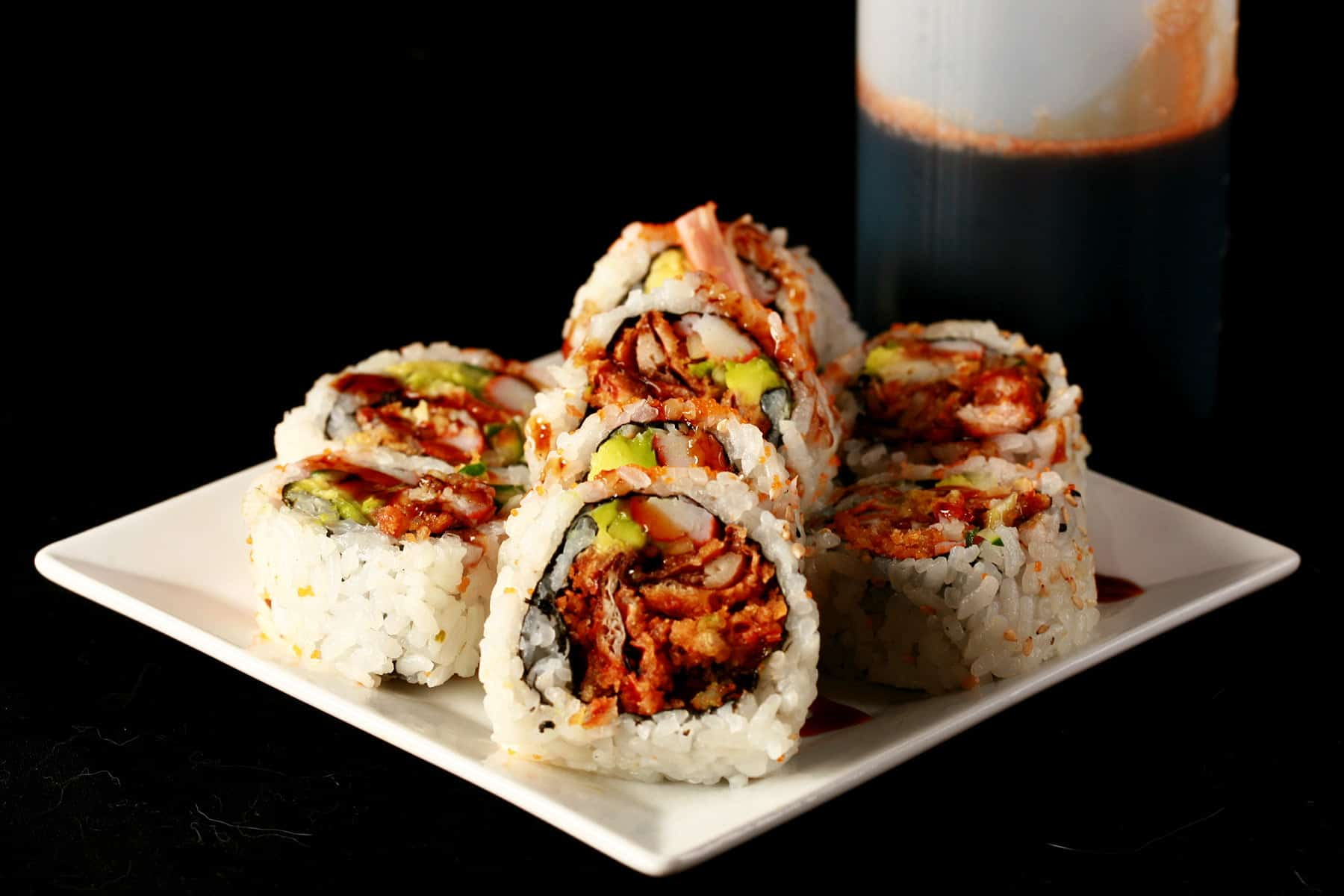 Close up image of a small plate of sushi, with brown sauce drizzled across it. There is a bottle of brown sauce - Eel Sauce for Sushi - behind the plate. This is one of 3 Sushi Sauce Recipes on this post.