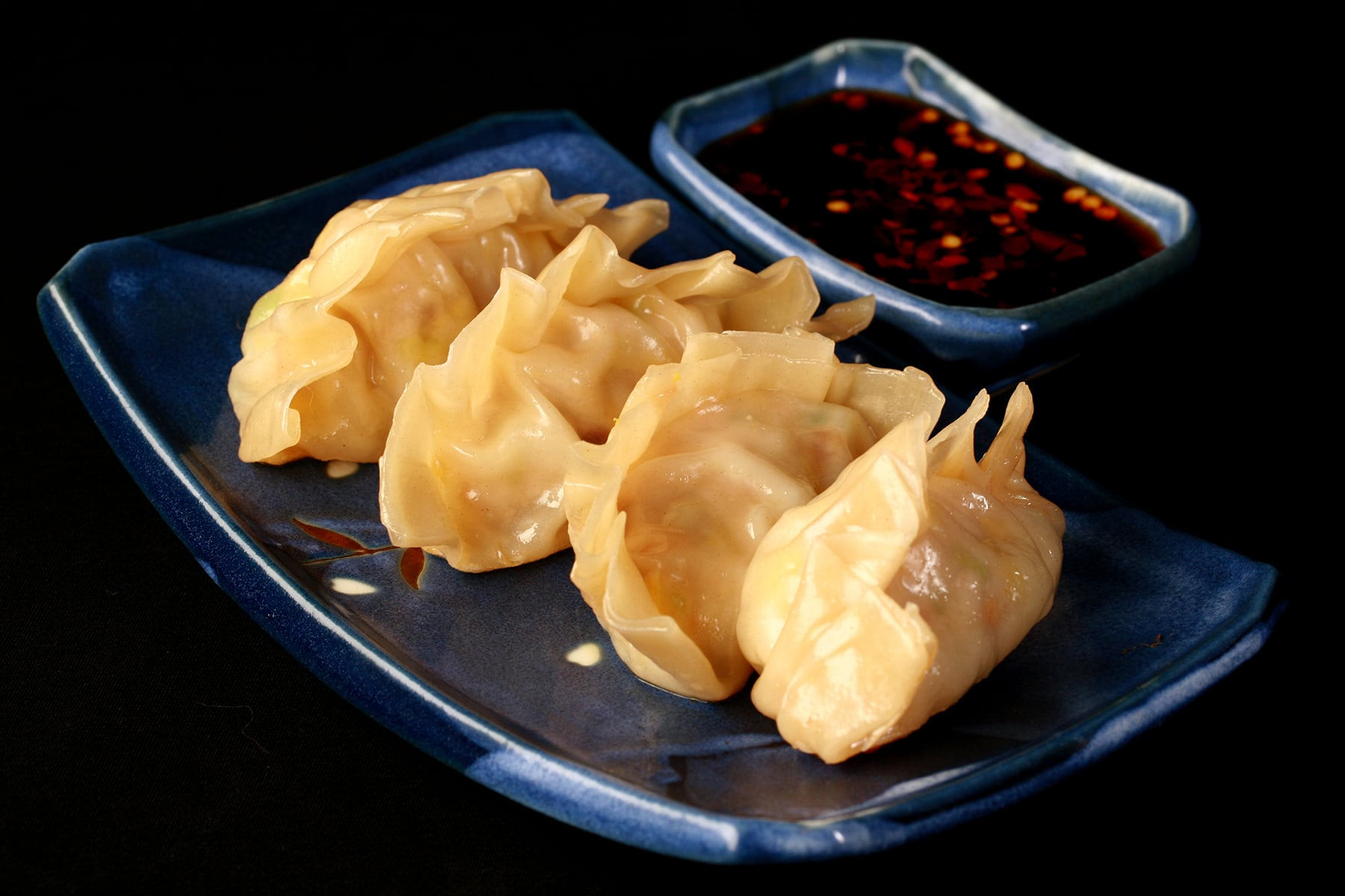4 homemade potstickers on a blue rectangular plate, with a small dish of pot sticker sauce next to it.