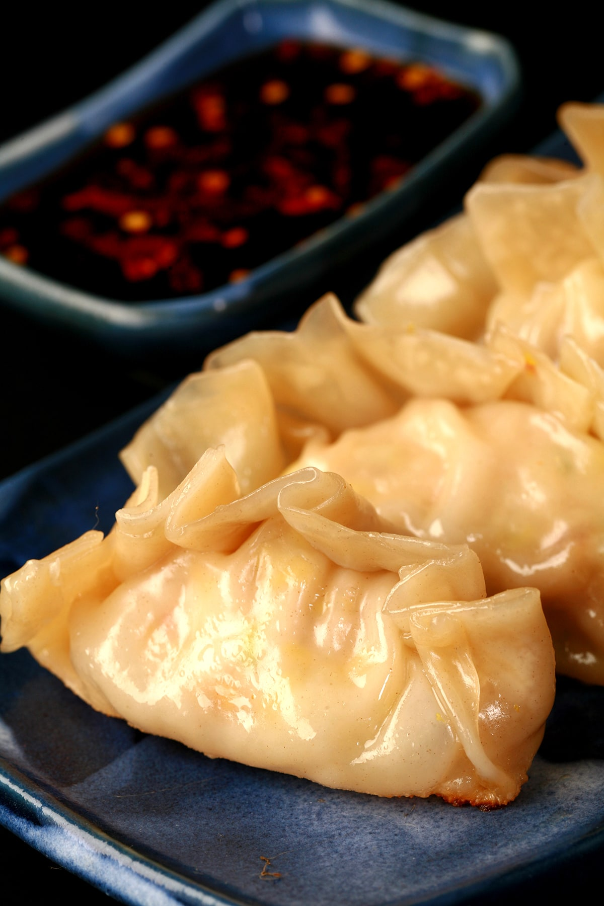 4 homemade gyoza on a blue rectangular plate, with a small dish of gyoza sauce next to it.