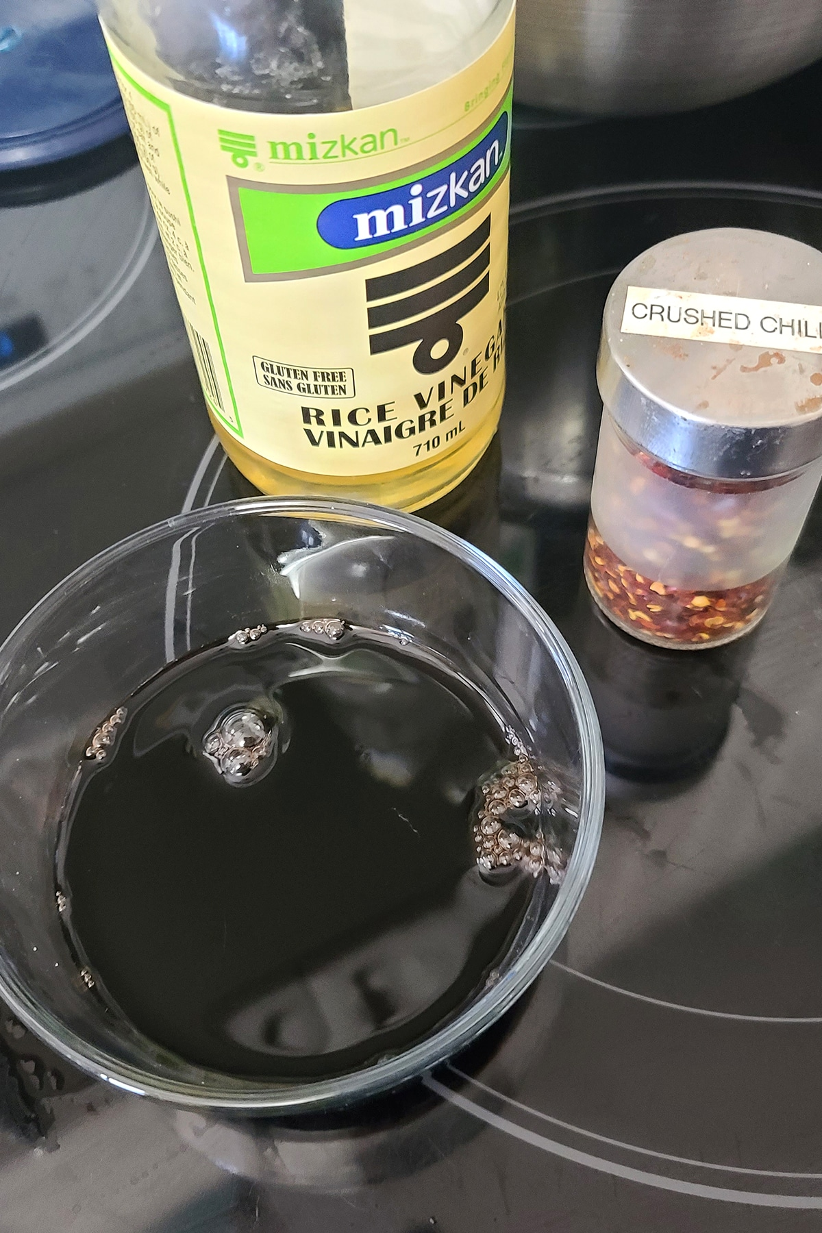 a small bowl of soy sauce with a bottle of rice vinegar and a shaker of crushed chilies.