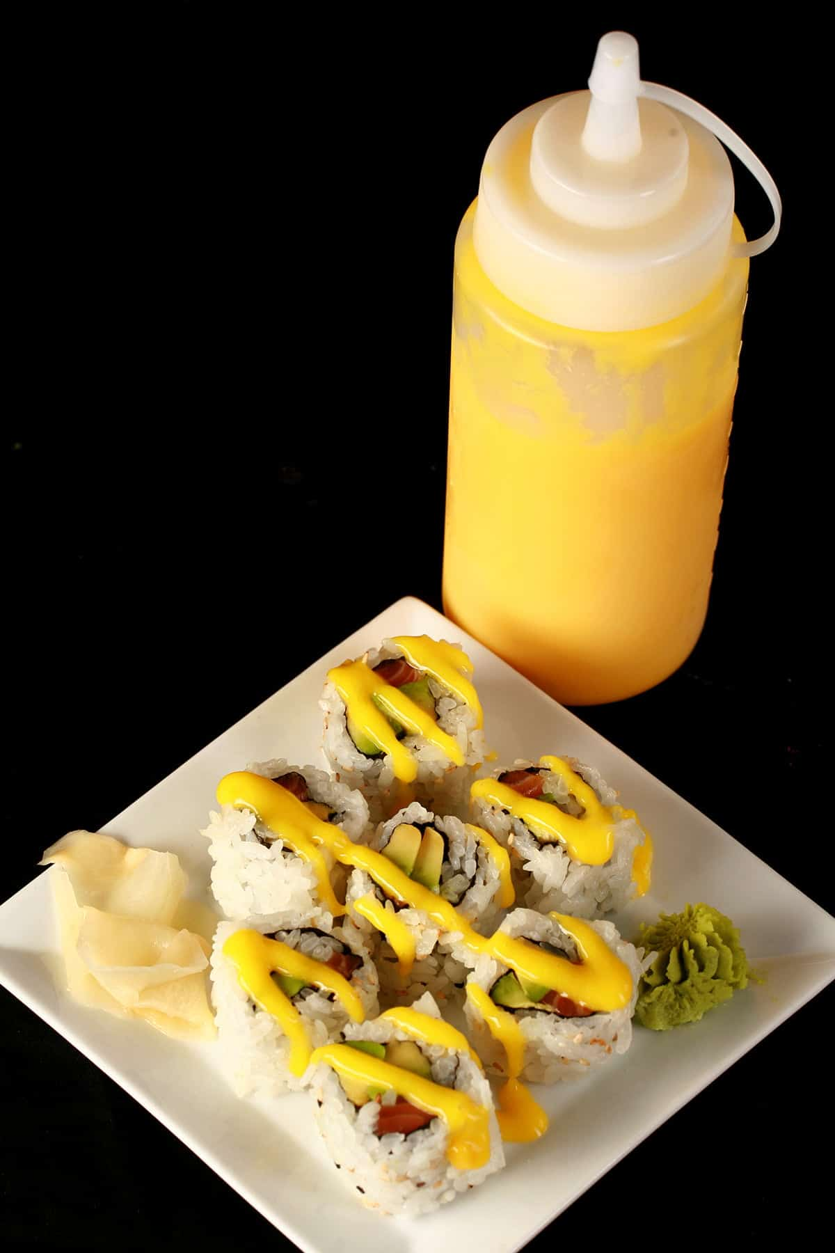 Close up image of a small plate of sushi, with yellow sauce drizzled across it. There is a bottle of yellow sauce - Mango Sauce for Sushi - behind the plate. This is one of 3 Sushi Sauce Recipes on this post.