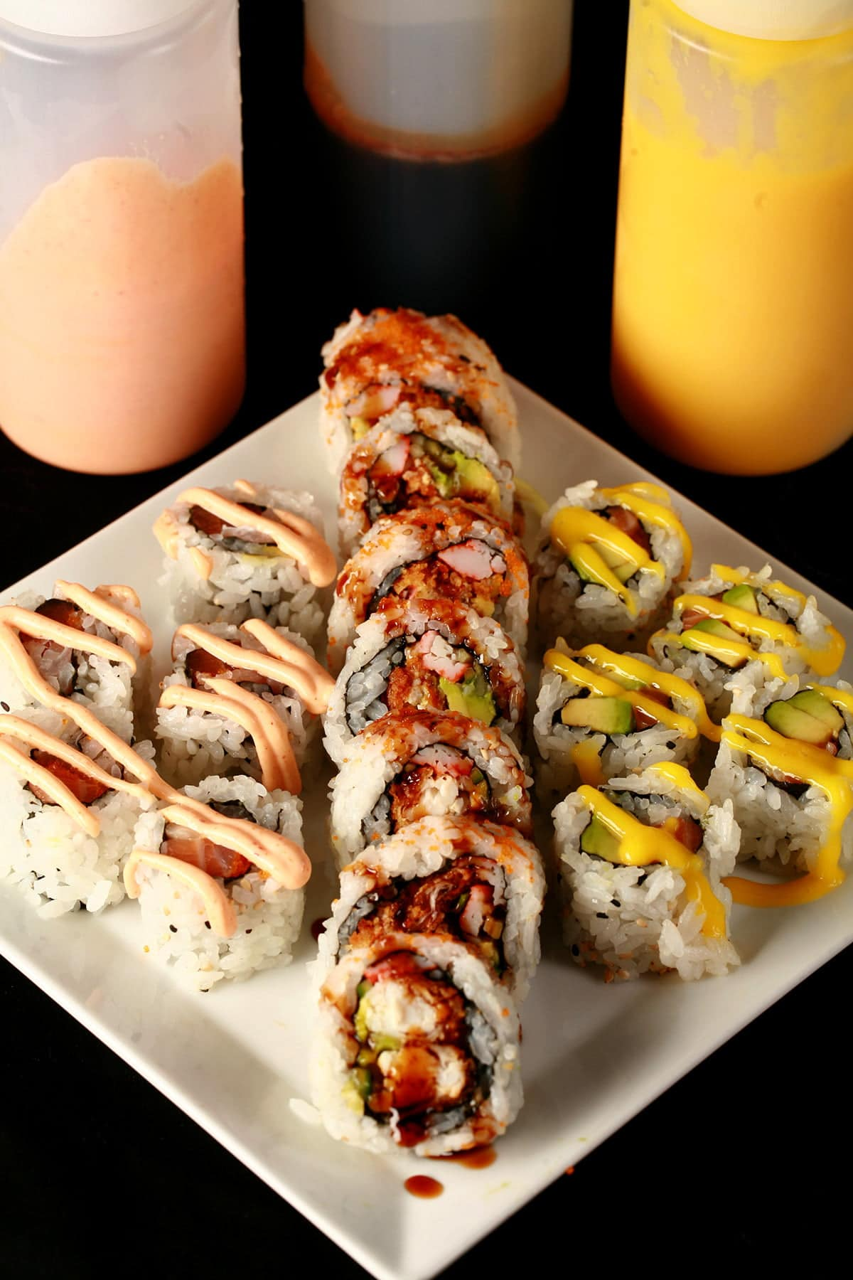 Close up image of 3 bottles of sauce - one yellow, one brown, and one pink. In front of the bottles is a plate of sushi, with the 3 colours of sauce drizzled across the sushi in squiggles