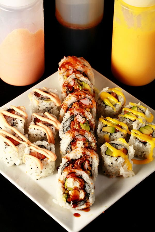 Close up image of 3 bottles of sauce - one yellow, one brown, and one pink. In front of the bottles is a plate, with the 3 colours of sauce drizzled across the sushi in squiggles