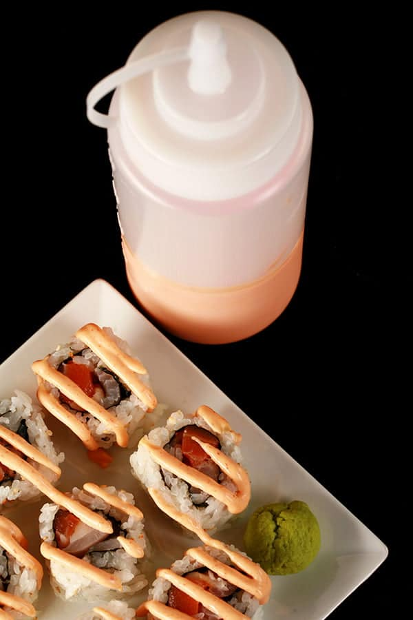 Close up image of a small plate of sushi, with creamy pink sauce drizzled across it. There is a bottle of the pink sauce - Dynamite Sauce for Sushi - behind the plate.