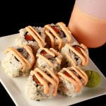 Close up image of a small plate of sushi, with creamy pink sauce drizzled across it. There is a bottle of the pink sauce - Dynamite Sauce for Sushi - behind the plate. This is one of 3 Sushi Sauce Recipes on this post.
