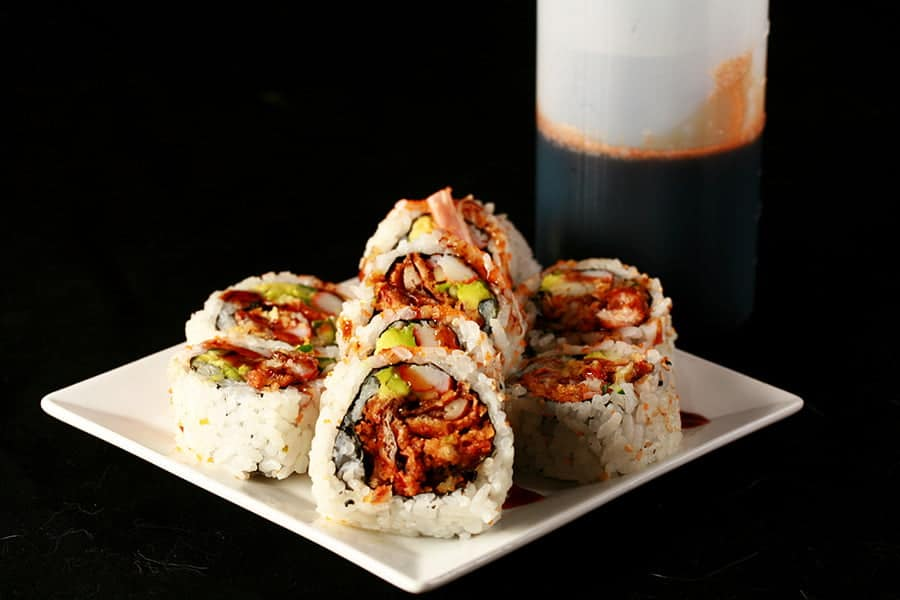 Close up image of a small plate of sushi, with brown sauce drizzled across it. There is a bottle of brown sauce - Eel Sauce for Sushi - behind the plate.