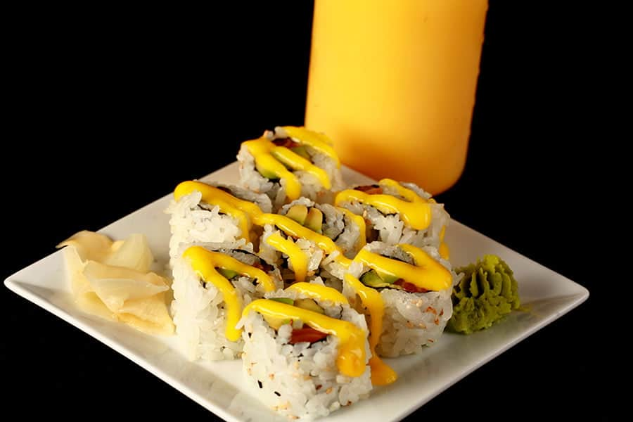 Close up image of a small plate of sushi, with yellow sauce drizzled across it. There is a bottle of yellow sauce - Mango Sauce for Sushi - behind the plate.