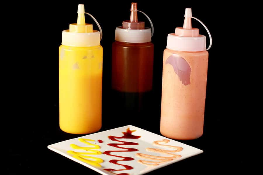 Close up image of 3 bottles of sauce - one yellow, one brown, and one pink. In front of the bottles is a plate, with the 3 colours of sauce drizzled across the plate in squiggles