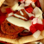 """Close up view of a vegetarian donair - a pita bread folded around a pile of vegan donair """"meat"""" slices, chopped red peppers, and donair sauce drizzled on top."""