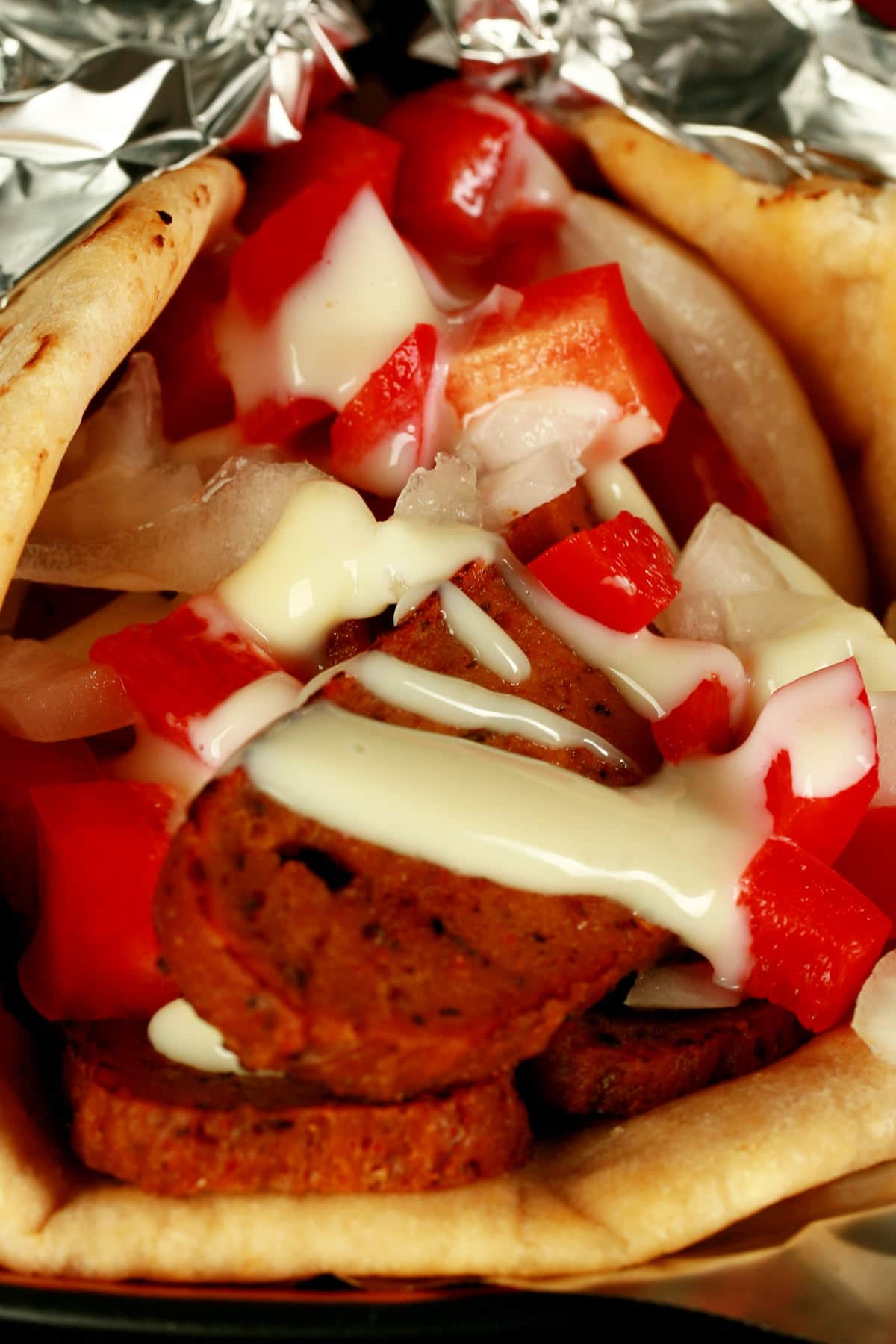 "Close up view of a vegan donair - a pita bread folded around a pile of vegan donair ""meat"" slices, chopped red peppers, and donair sauce drizzled on top."