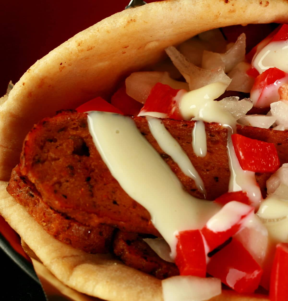 "Close up view of a vegetarian donair - a pita bread folded around a pile of vegan donair ""meat"" slices, chopped red peppers, and donair sauce drizzled on top."