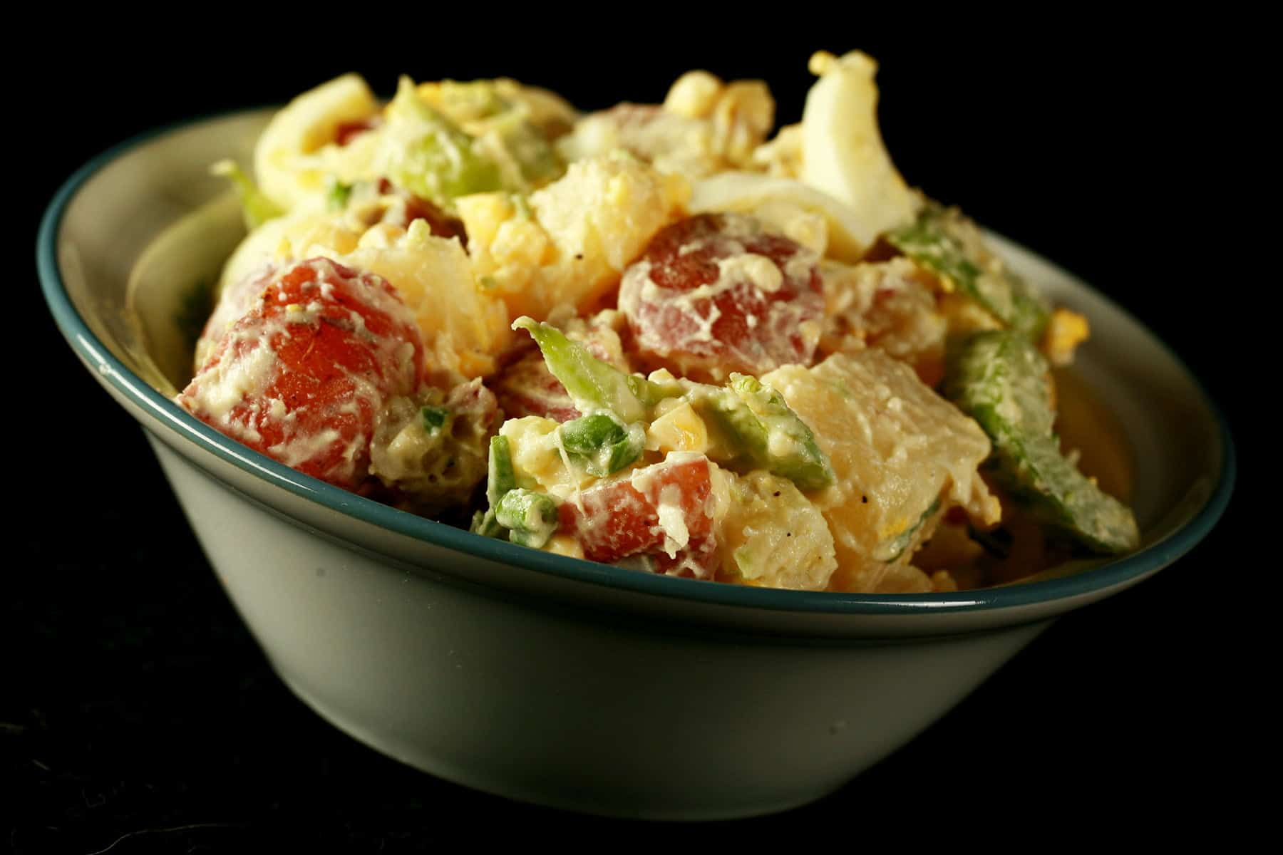 A bowl of a creamy smoked potato salad. Chunks of red potatos, celery slices, and hard boiled egg are all visible.
