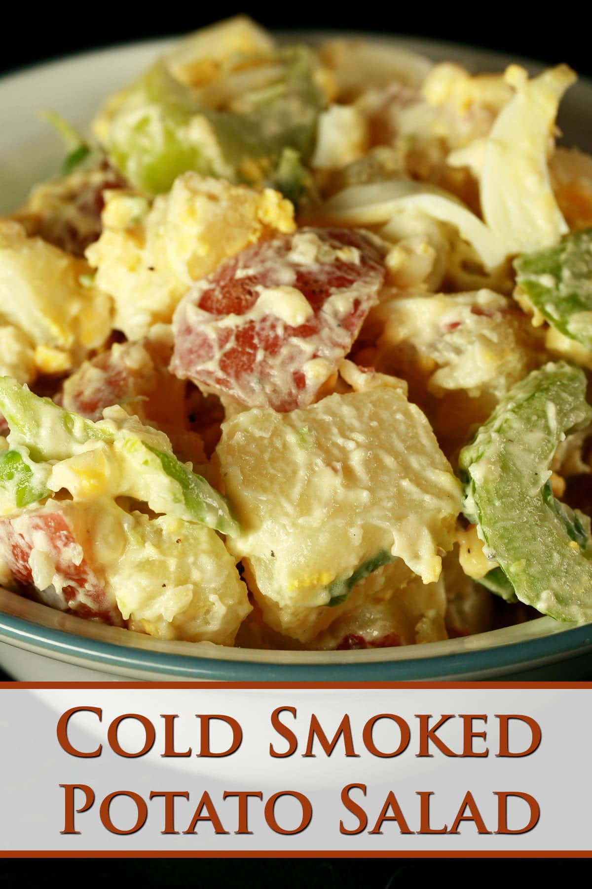 A bowl of a creamy cold-smoked potato salad. Chunks of red potatos, celery slices, and hard boiled egg are all visible.