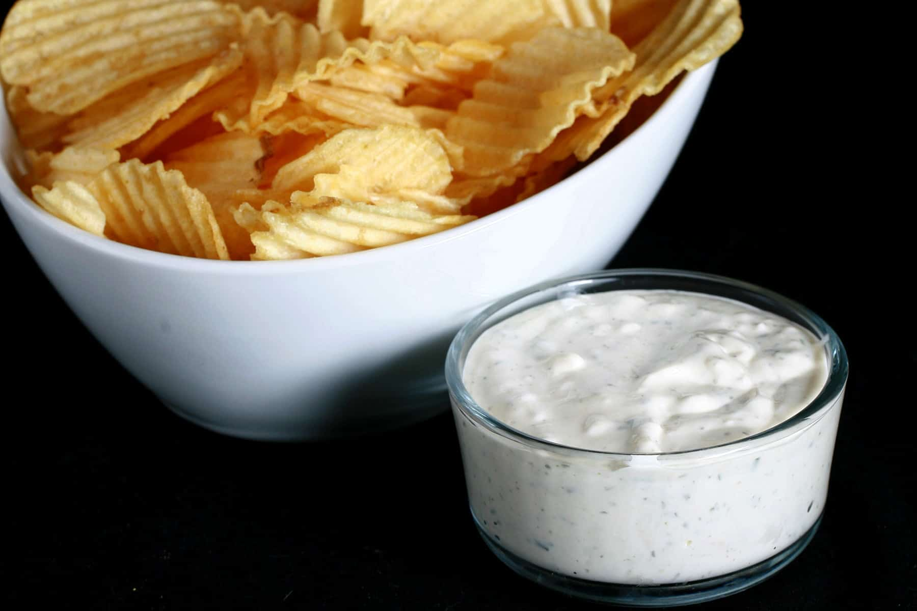 A large bowl of ripple chips is pictured next to a bowl of Dill Pickle Cream Cheese Dip.