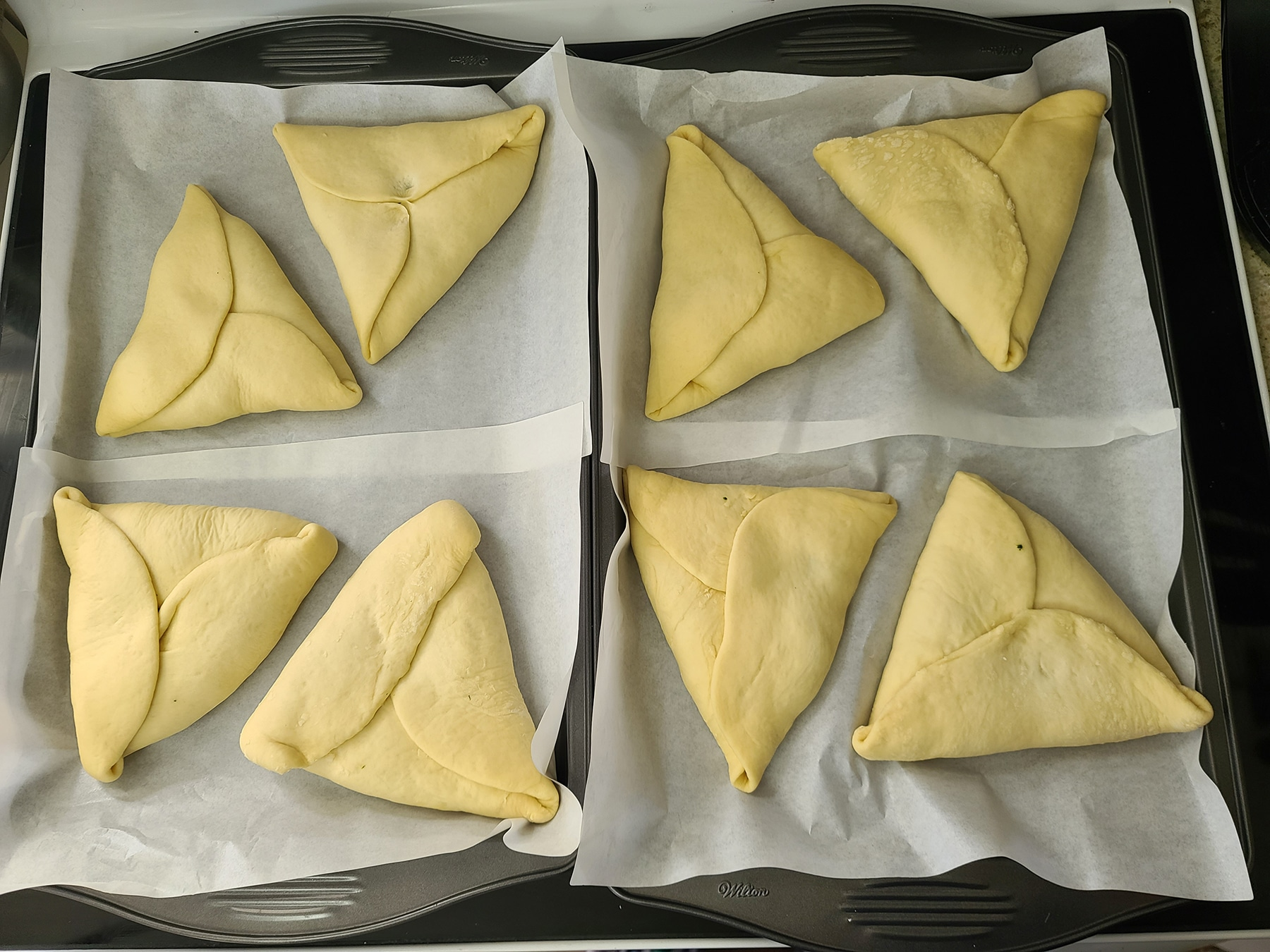 8 unbaked spinach hand pies, on 2 parchment lined baking sheets.