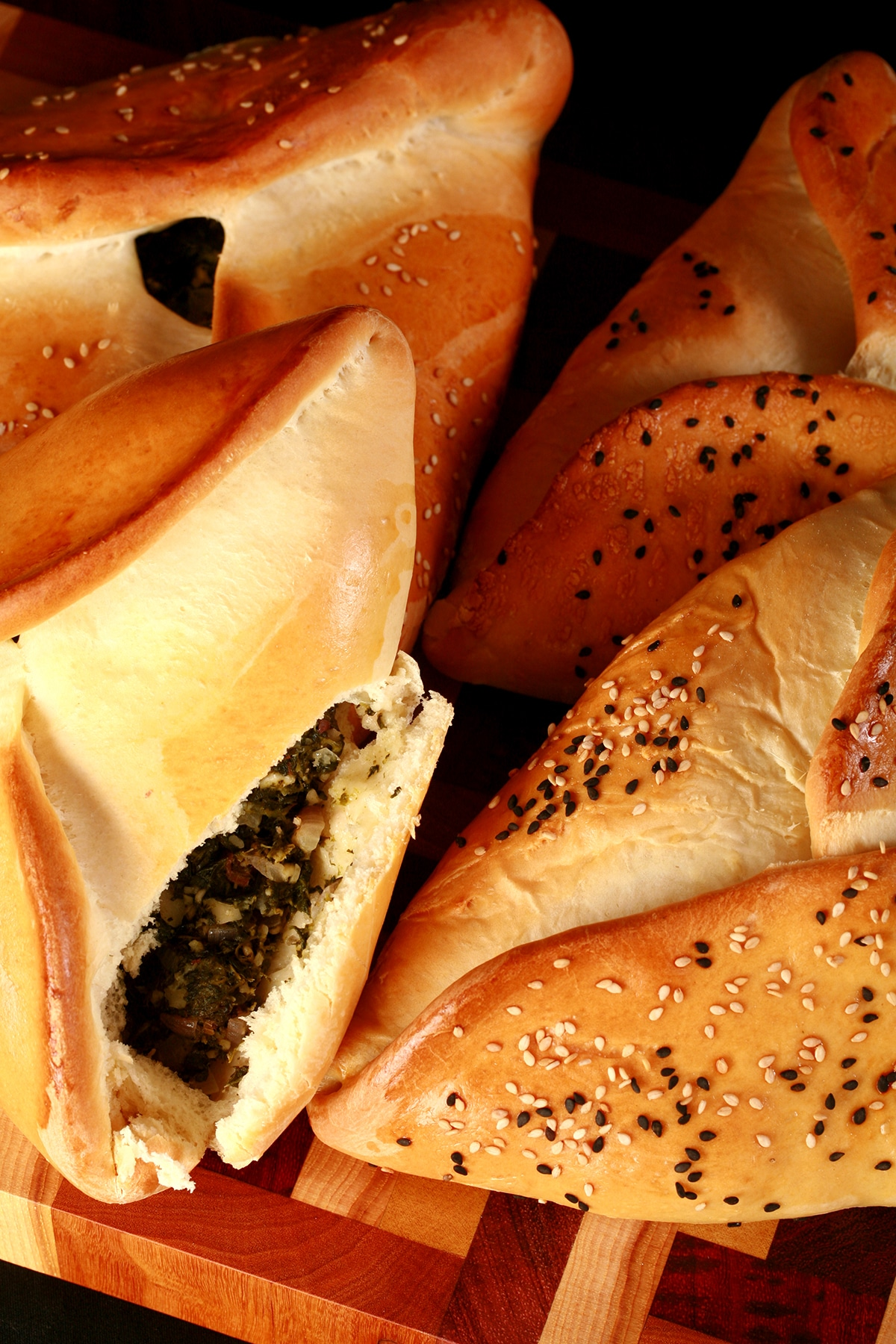 Close up view of 4 bread based spinach hand pies, covered with sesame seeds. One is opened, revealing the spinach and feta filling.